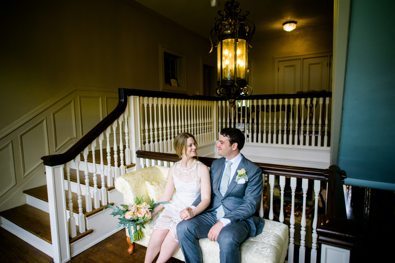 Grand staircase portrait of the couple during a Cheney Mansion wedding in Oak Park.
