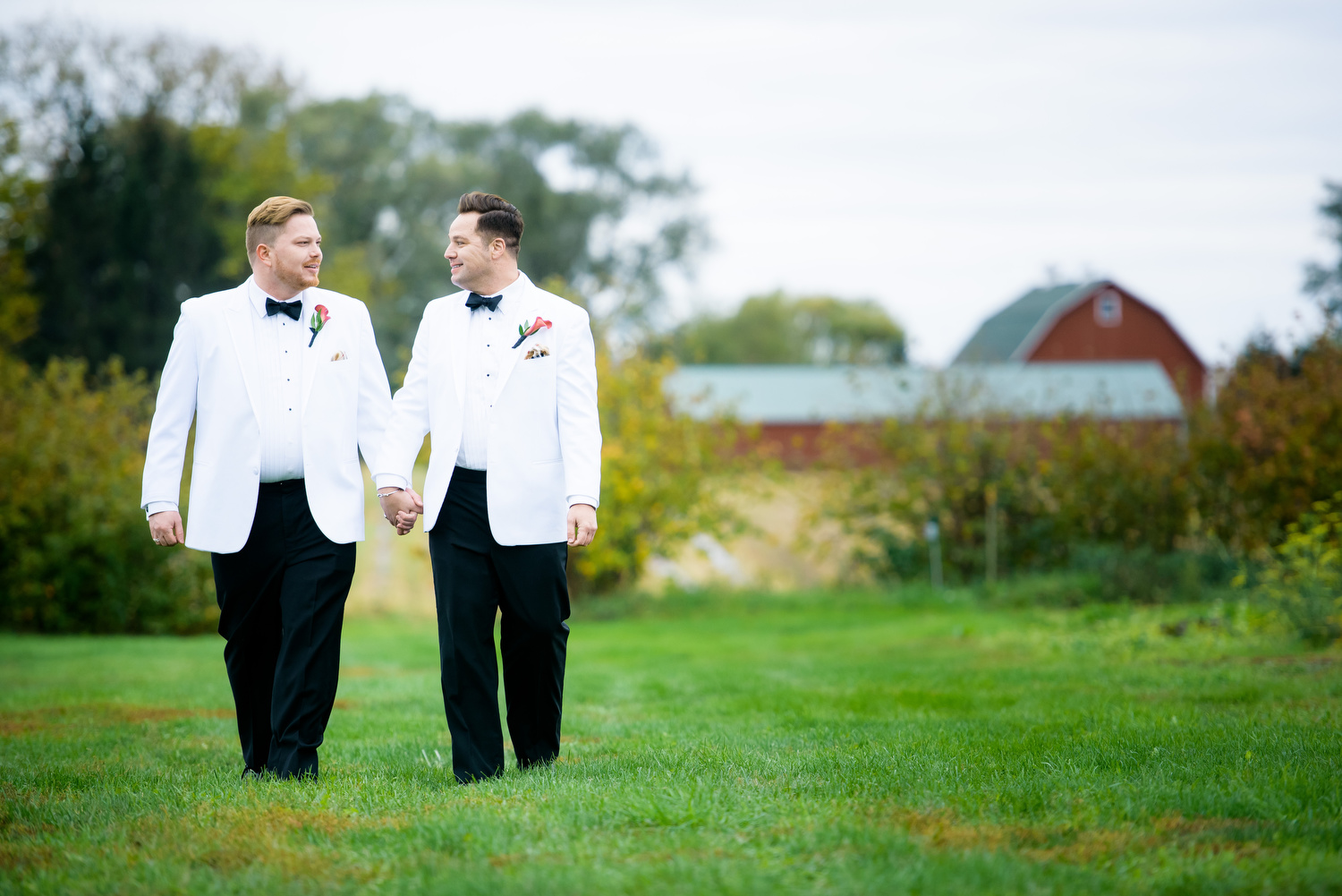 Portrait of the grooms at Heritage Prairie Farm during their wedding.