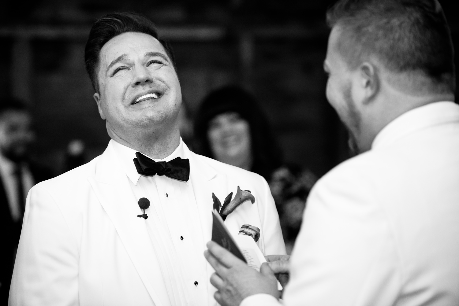 Grooms laugh during their wedding ceremony at Heritage Prairie Farm.