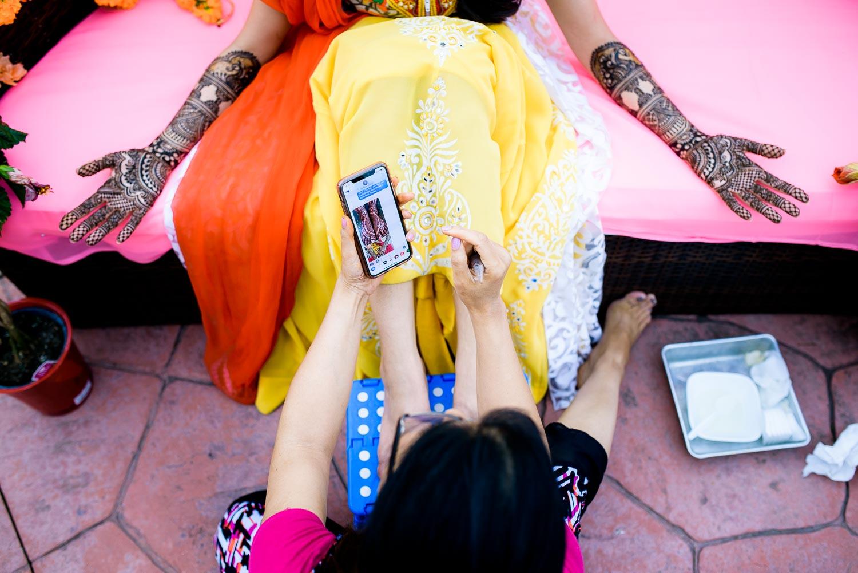 Henna artist, Henna Moments, during an Indian wedding mehndi in South Barrington, Illinois.