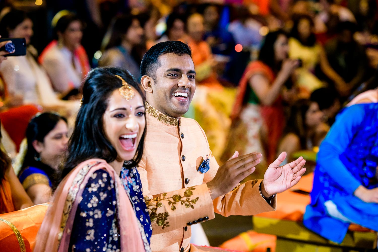 Bride and groom share a laugh during an Indian wedding sangeet at Stonegate Banquets in Hoffman Estates.