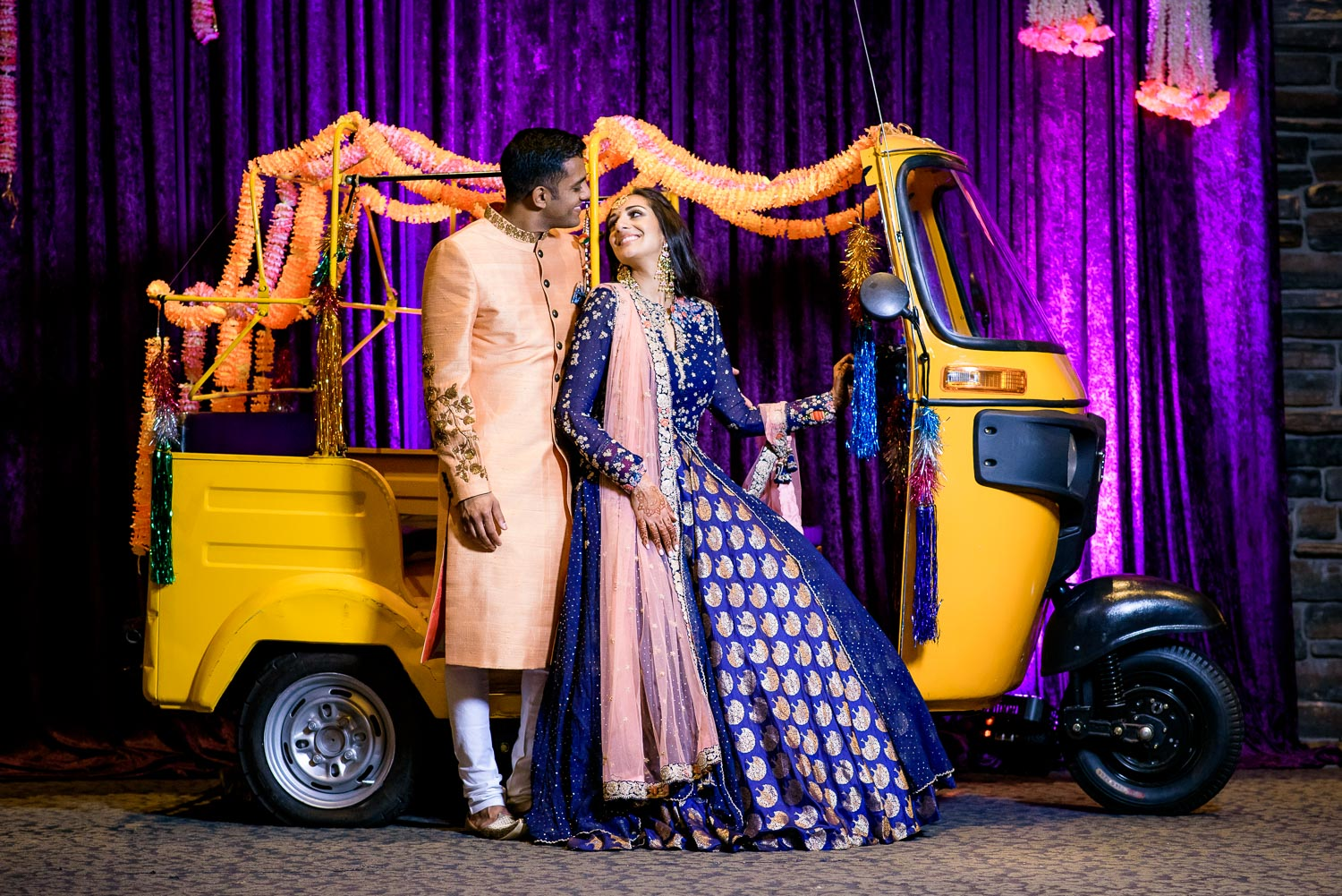 Bride and groom portrait with rickshaw during an Indian wedding sangeet at Stonegate Banquets in Hoffman Estates.