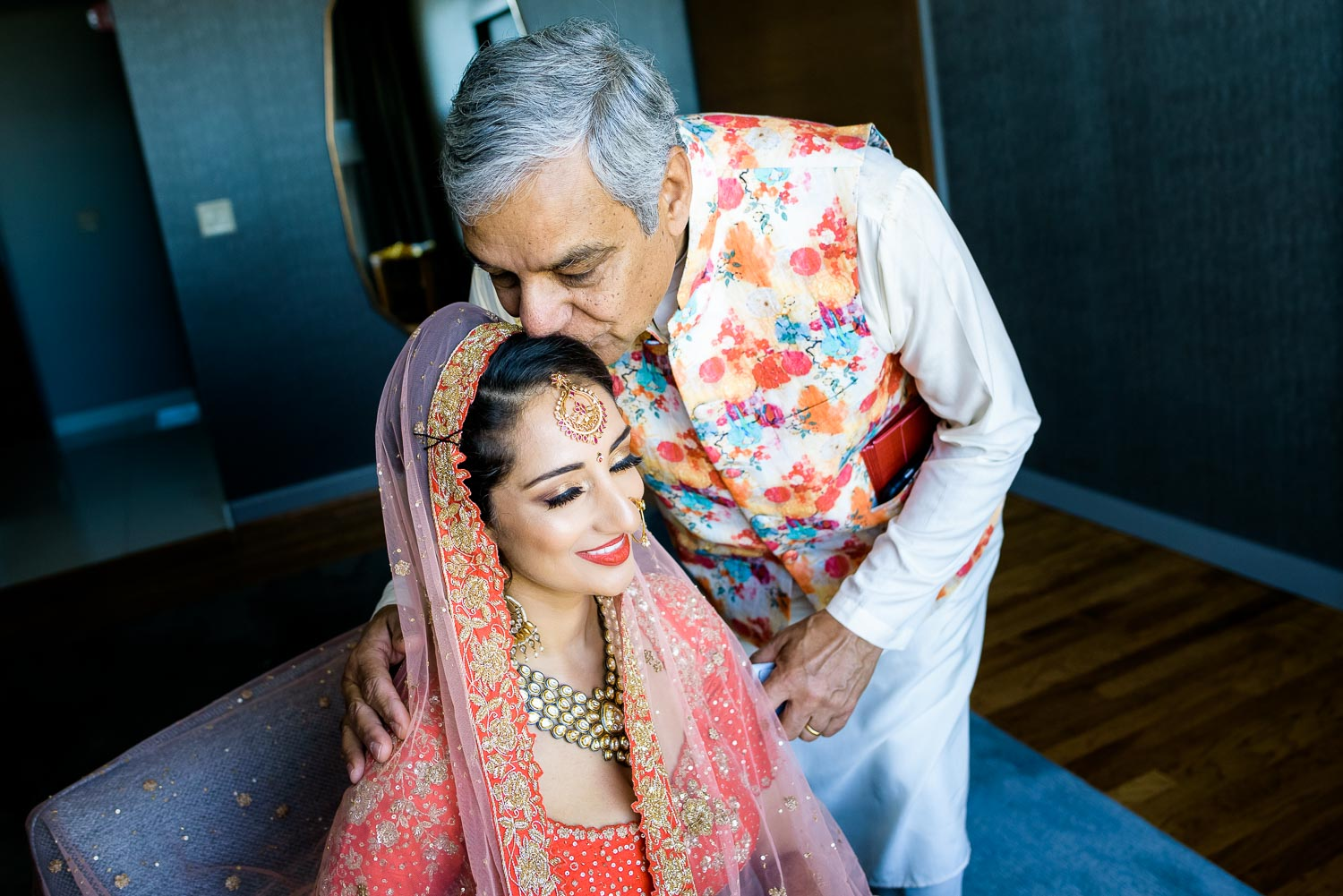 Father kisses the bride before her Renaissance Schaumburg Convention Center Indian wedding.