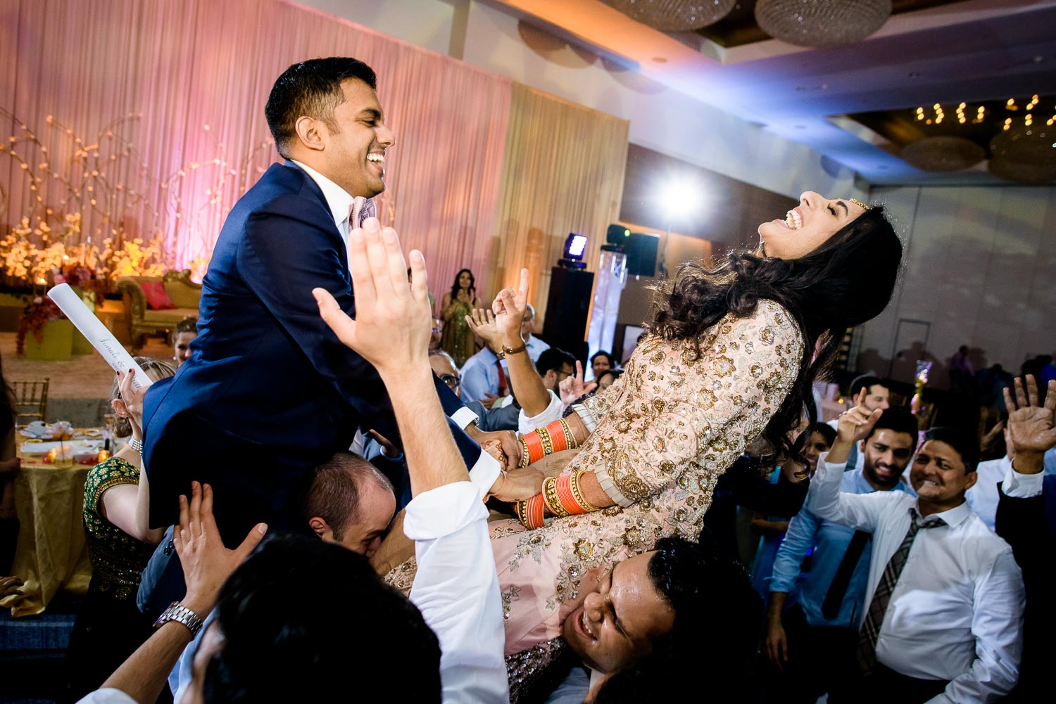 Bride and groom raised in the air during a Renaissance Schaumburg Convention Center Indian wedding reception.
