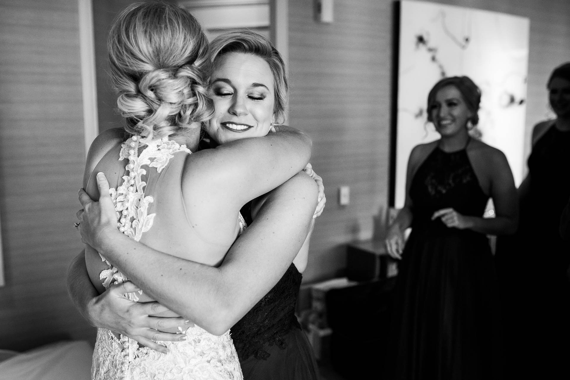 Bride and bridesmaid hug while getting ready before a Mid America Club wedding in Chicago.