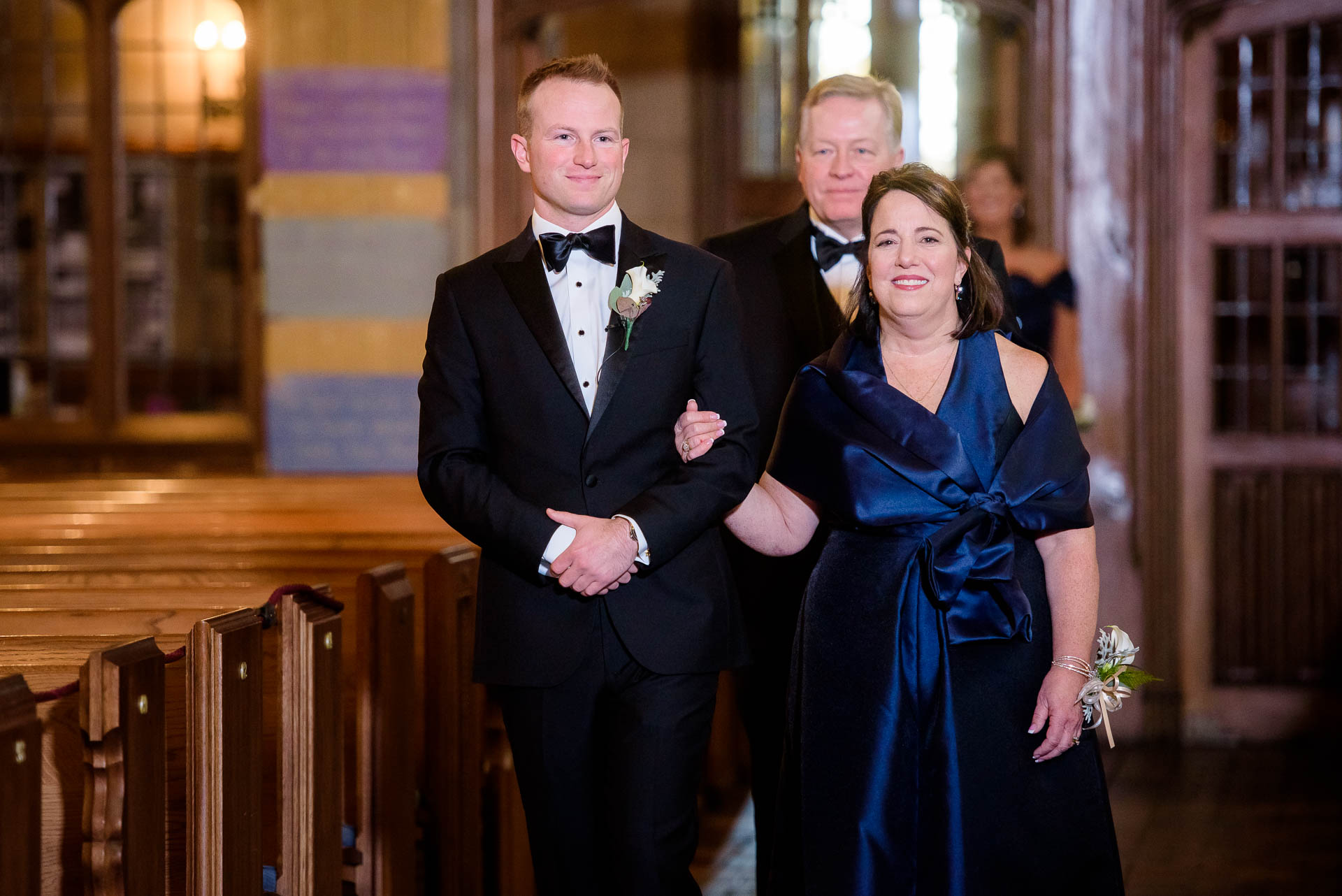 Groom and mother walk down the aisle during a wedding ceremony at Fourth Presbyterian Church in Chicago.