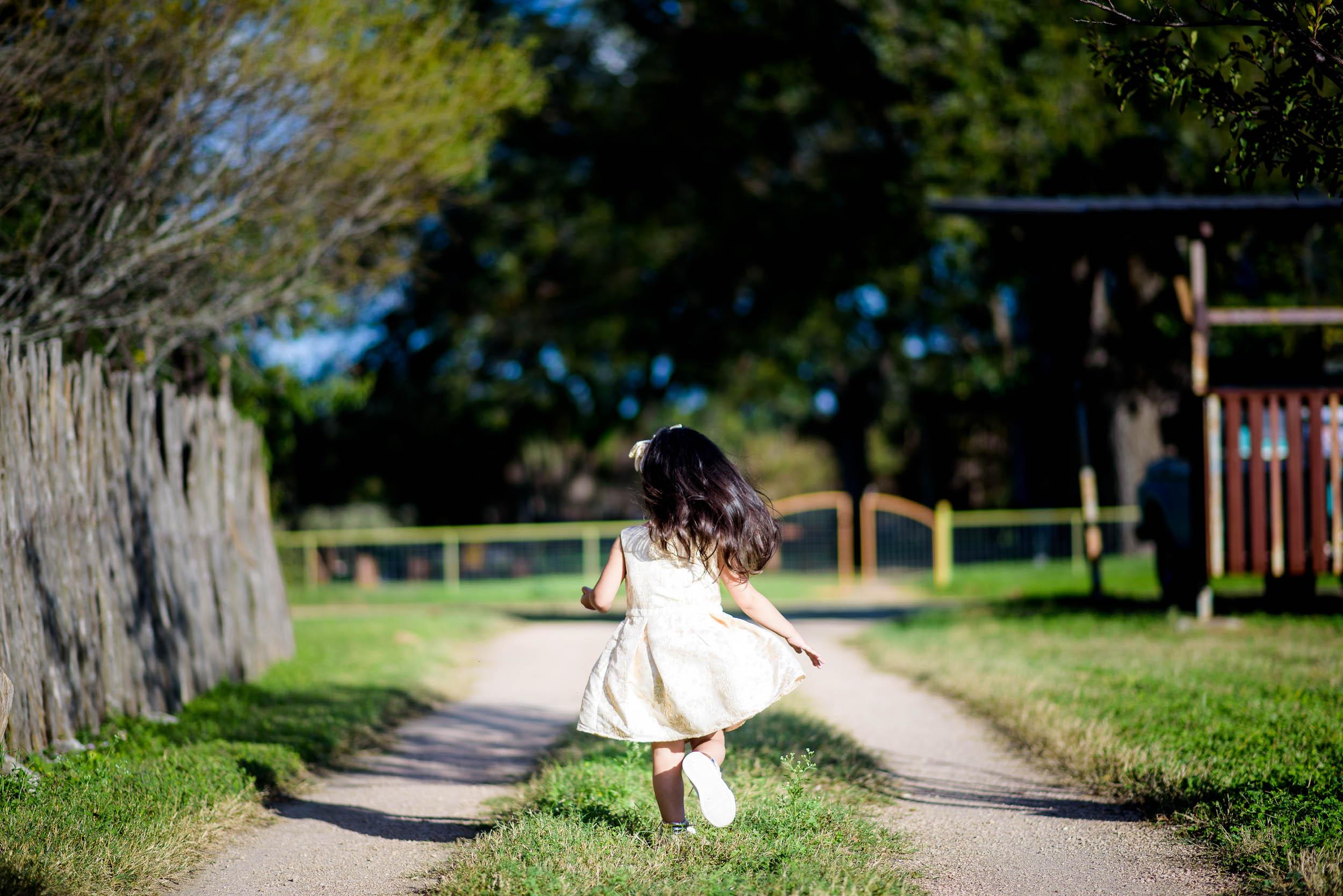 Flower girl runs around before a Montesino Ranch wedding Austin, Texas.