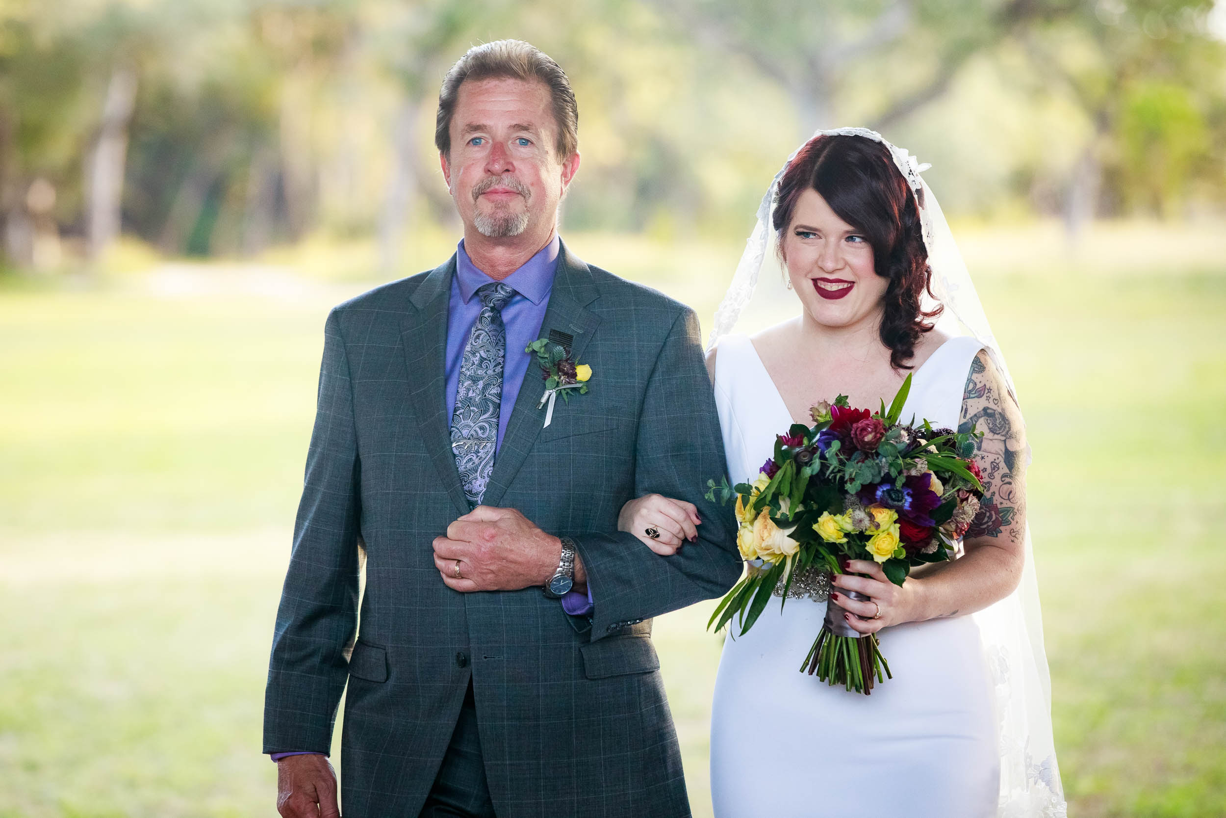 Bride and father walk down the aisle during a Montesino Ranch wedding Austin, Texas.