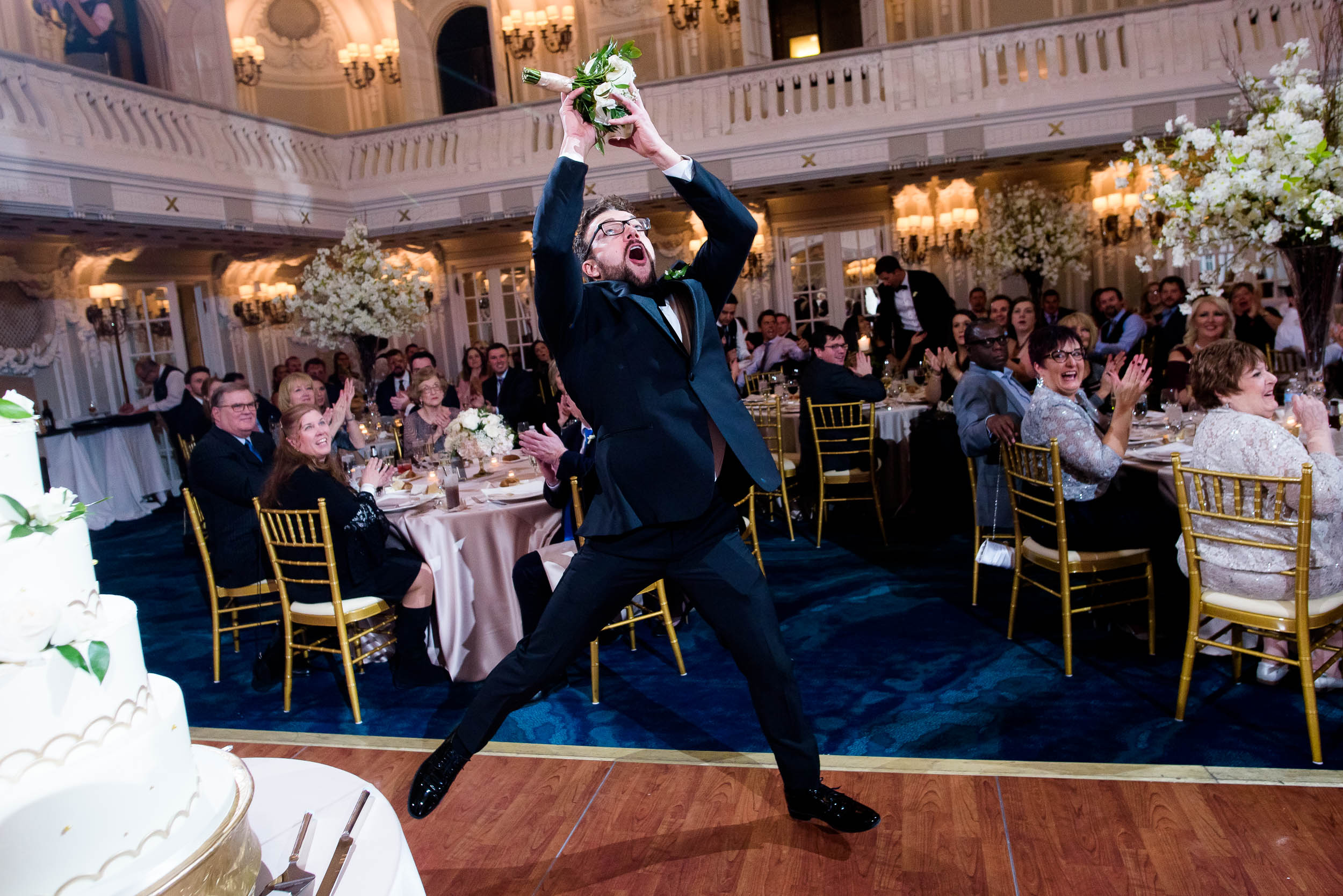 Groomsman catches a bouquet during a Blackstone Chicago wedding.