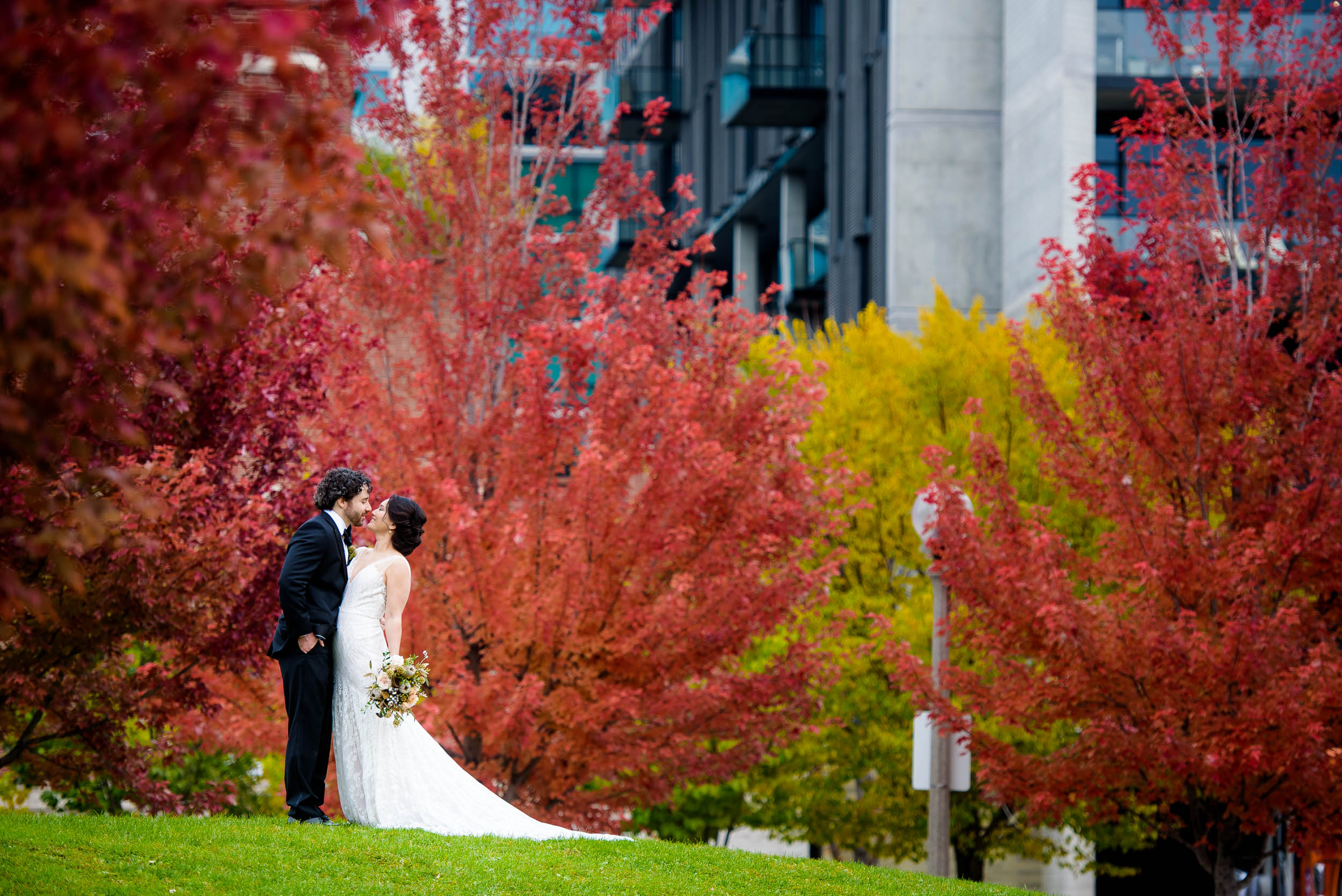 Bride and groom kiss amongst the fall colors at Mary Bartelme Park.