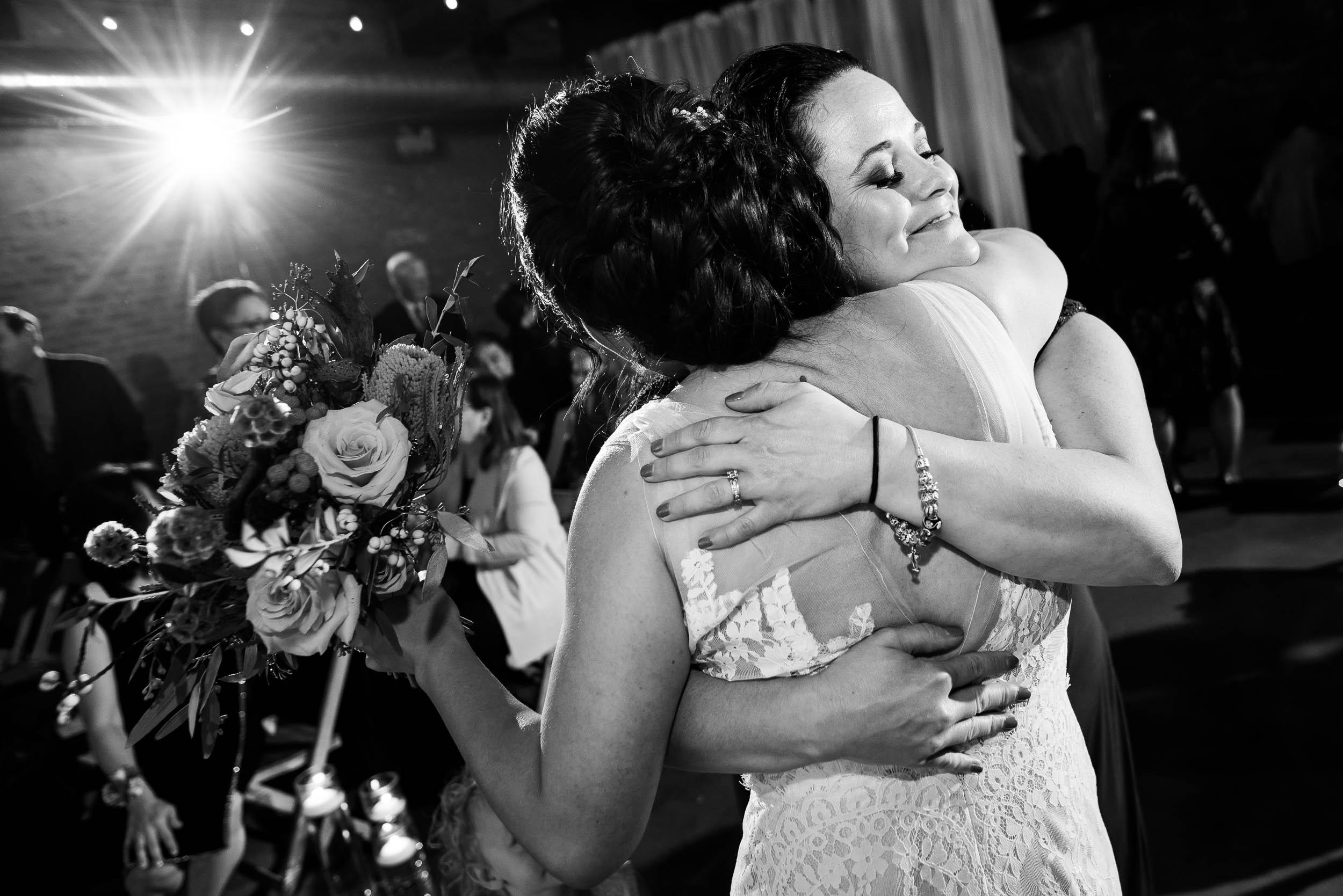 Sisters hug during a Loft on Lake Chicago wedding.
