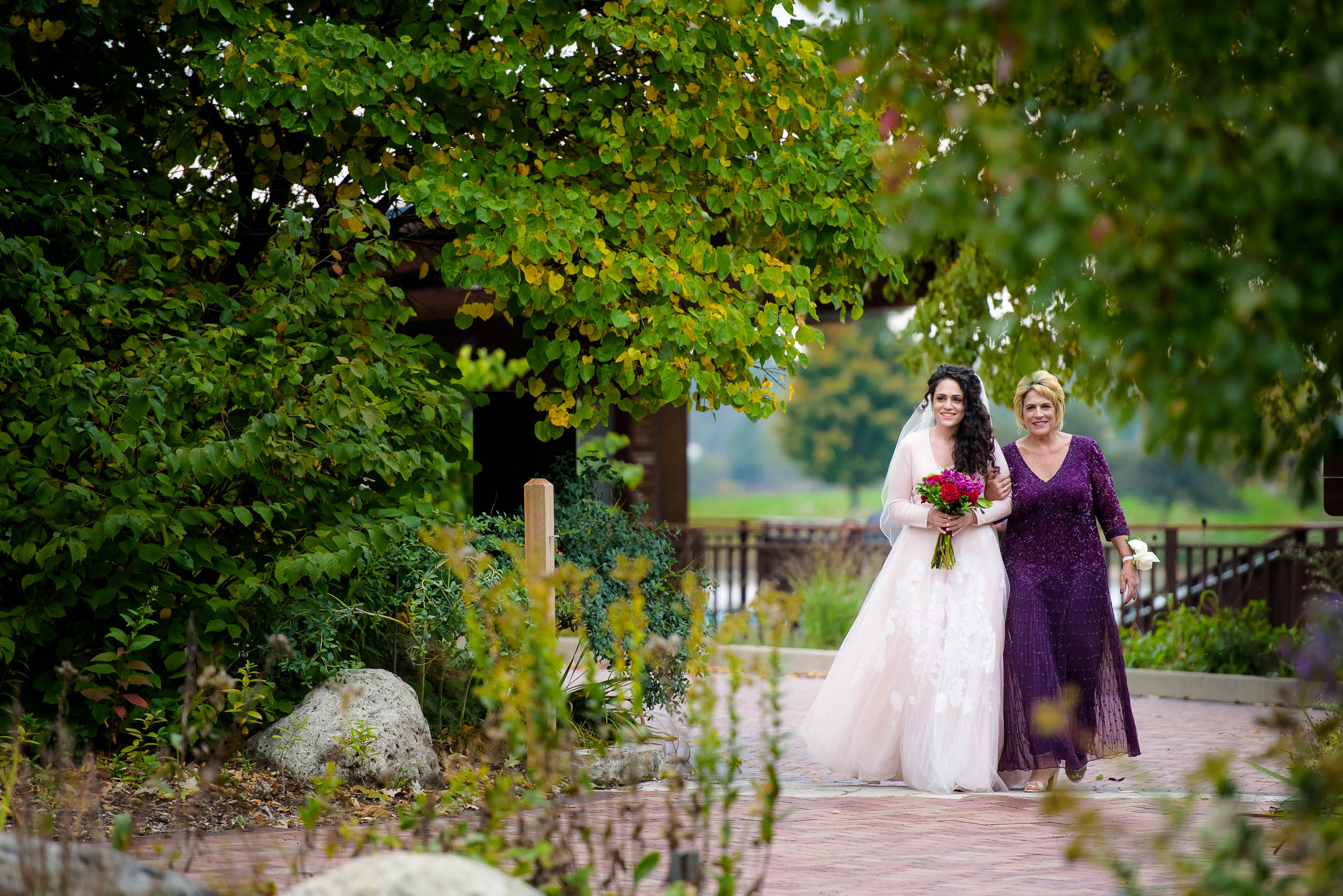 Bride walks down the aisle with her mother during an Independence Grove Chicago wedding.