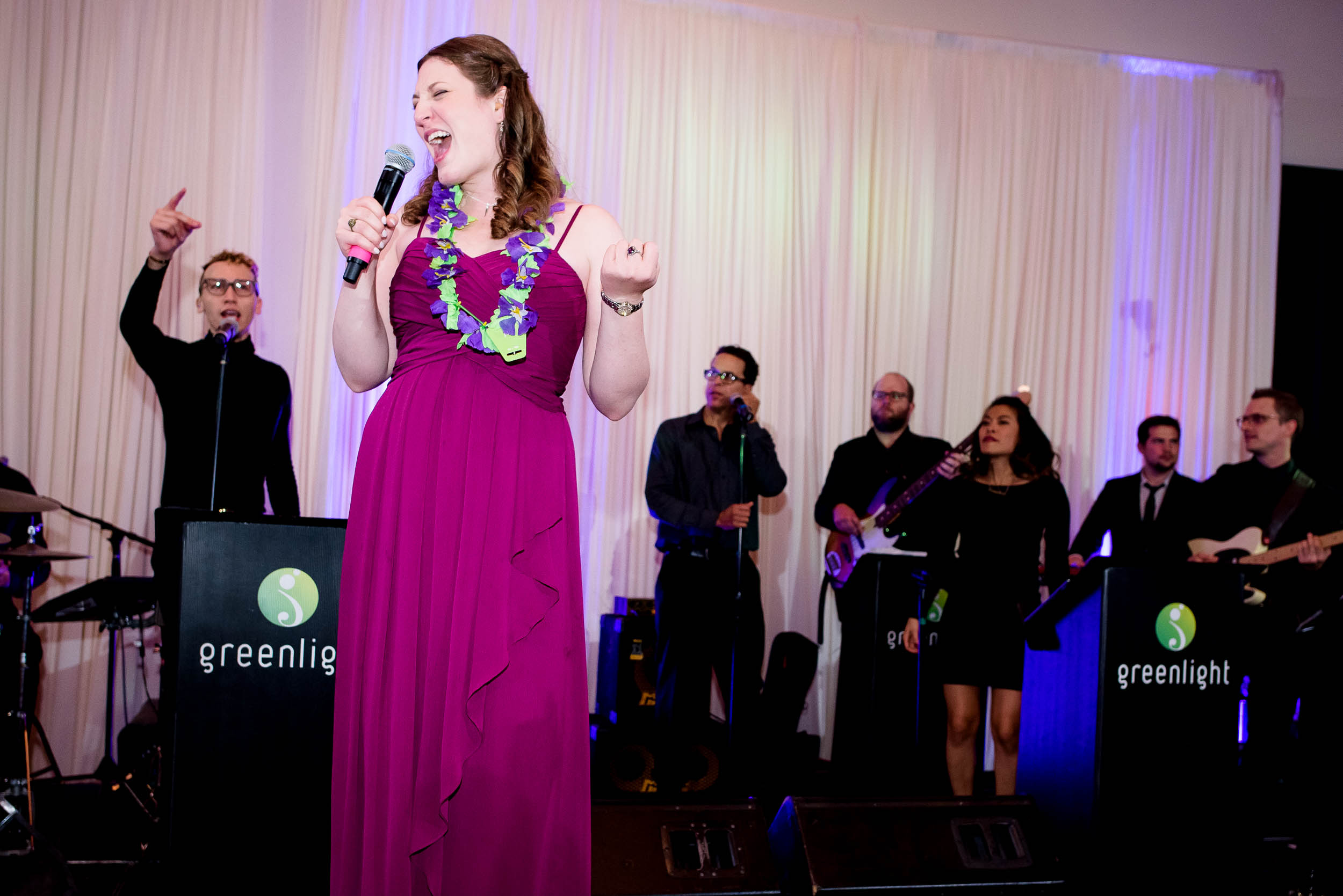 Maid of honor sings with Greenlight band during an Independence Grove Chicago wedding.