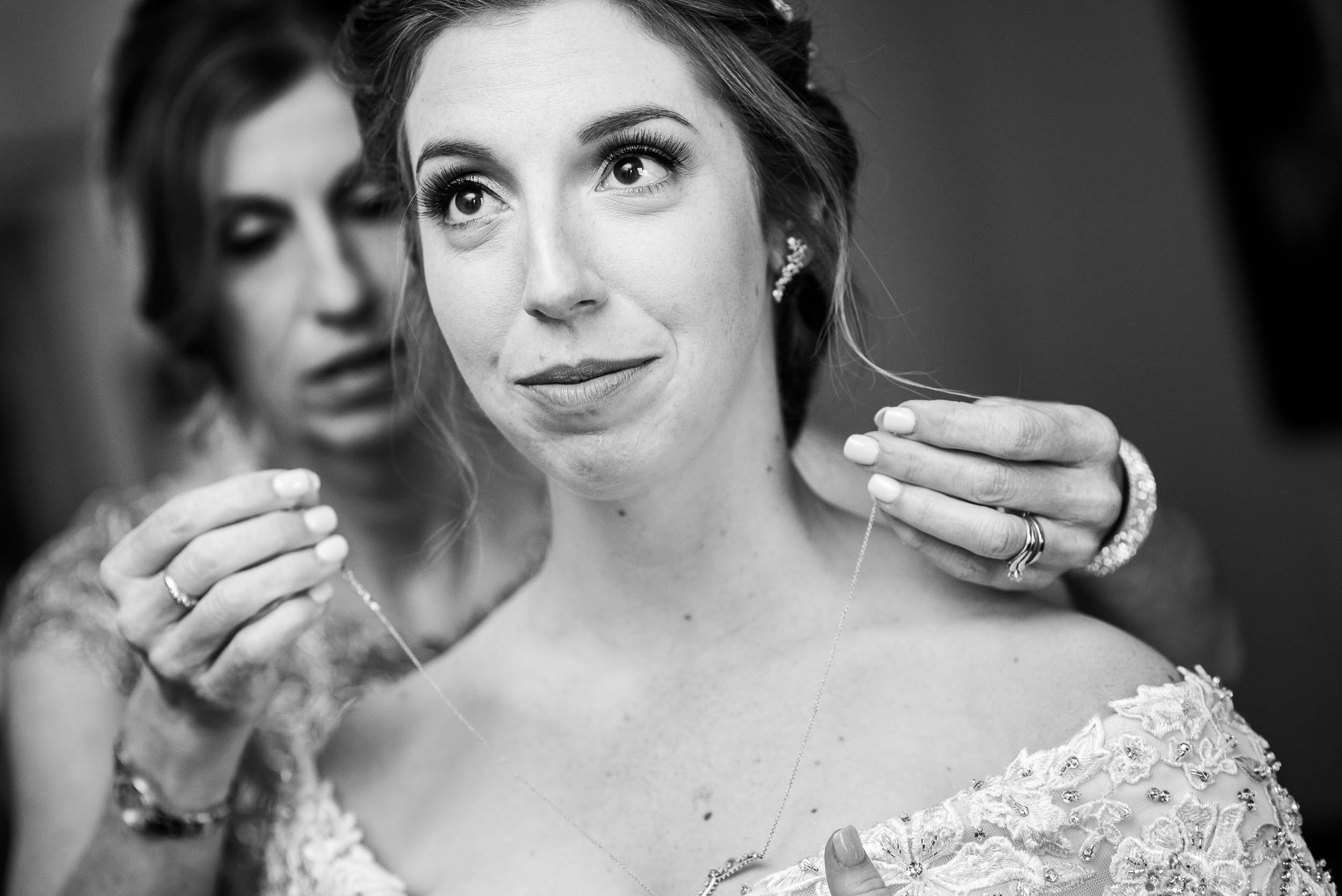 Mom helps the bride with her jewelry during a Newberry Library Chicago wedding.