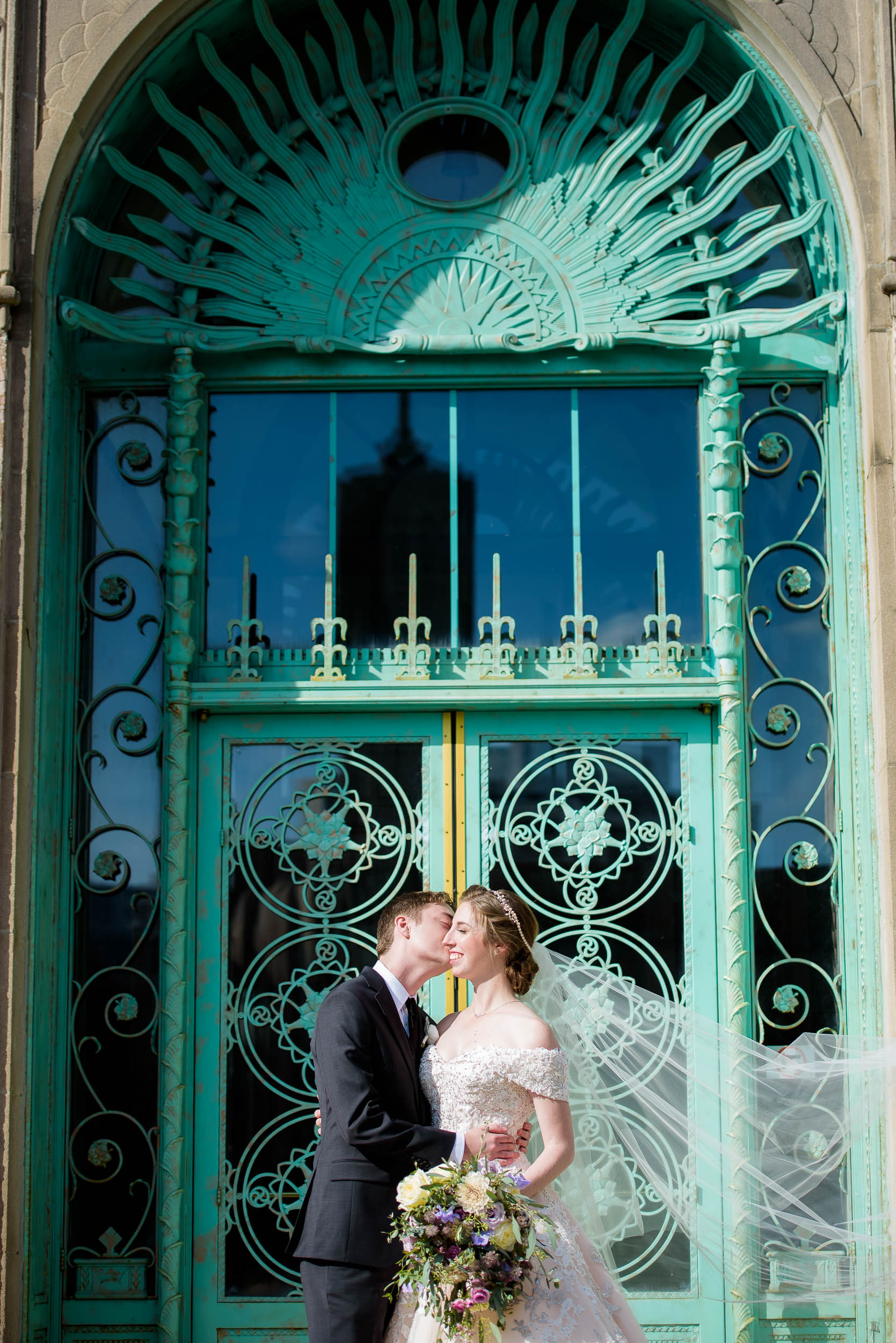 Wedding day portrait outside the green doors of Loyola's Cudahy Library.