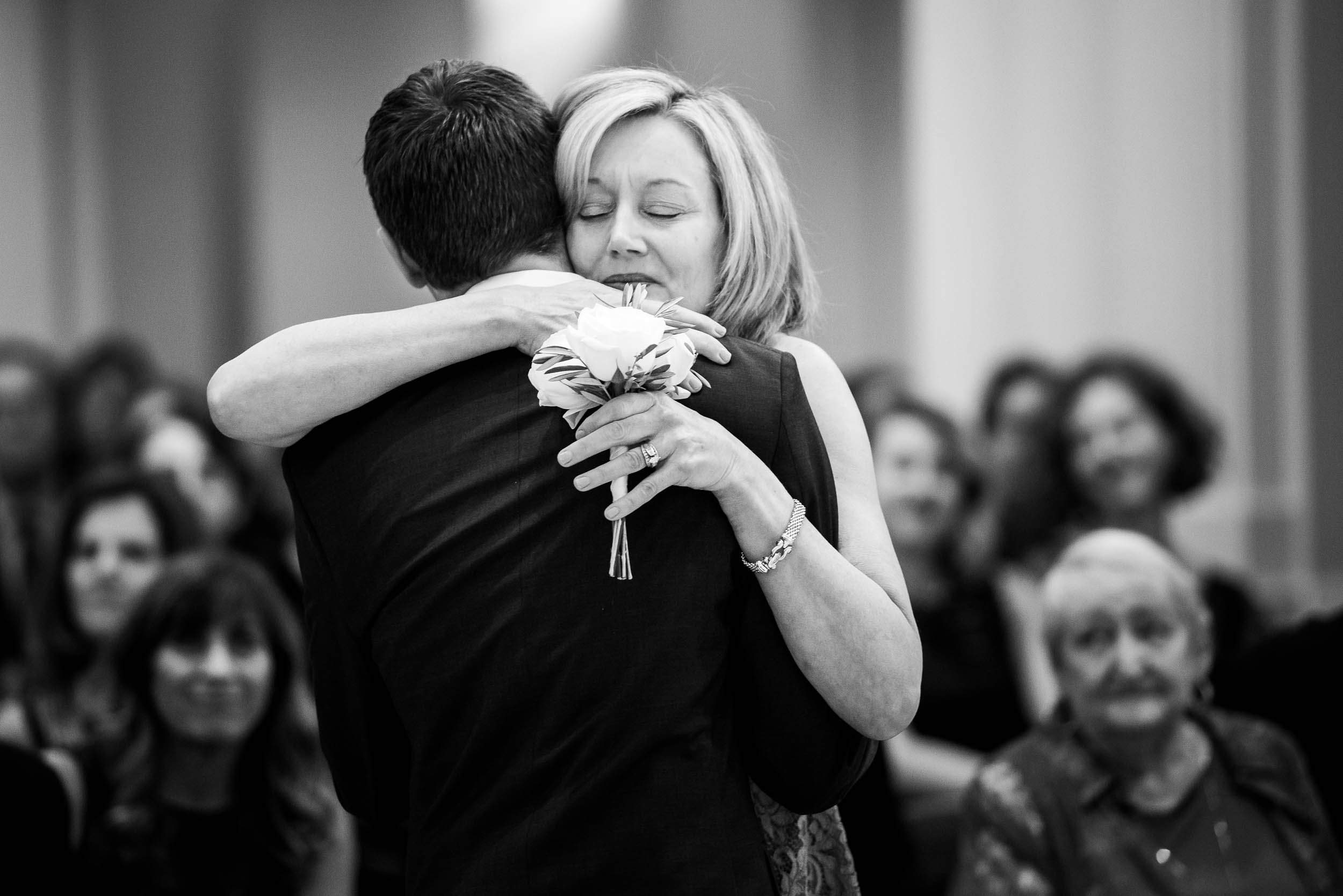 Mother and groom hug during a wedding ceremony at Madonna Della Strada.