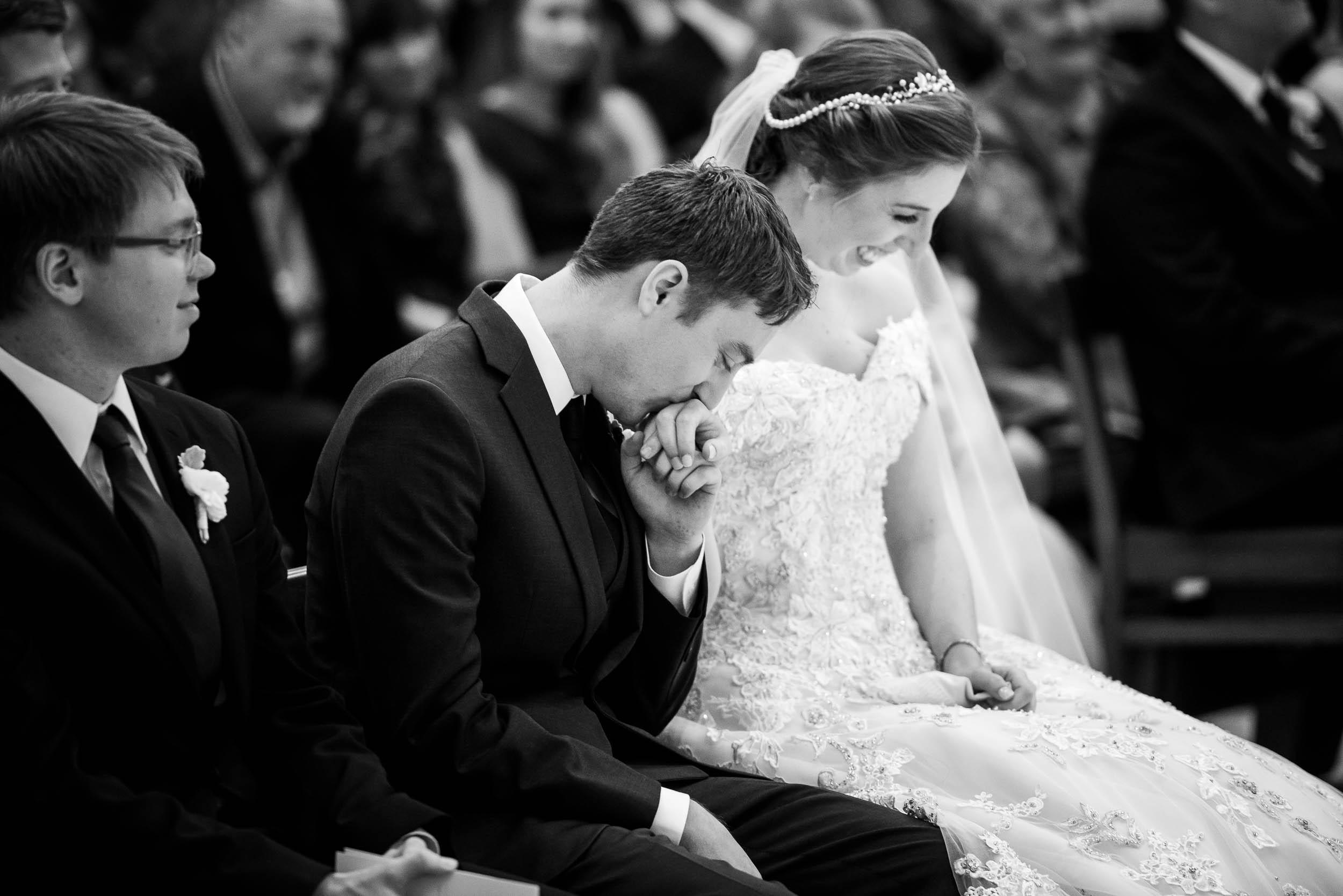 Groom kisses his brides hand during a wedding ceremony at Madonna Della Strada.