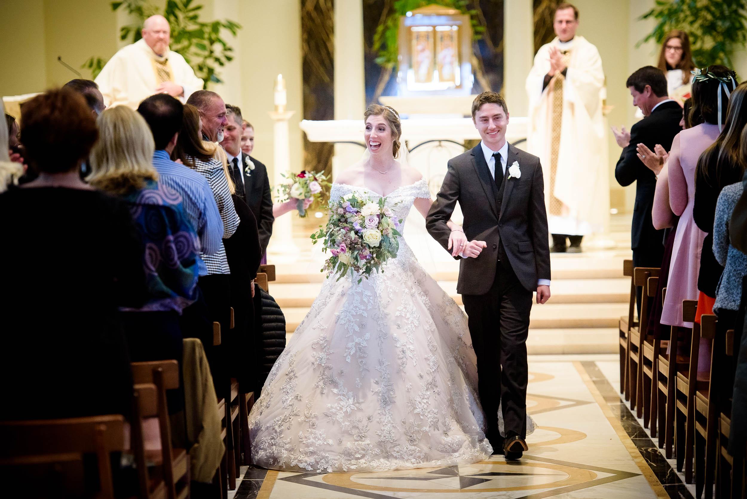 Bride and groom walk down the aisle during a wedding ceremony at Madonna Della Strada.
