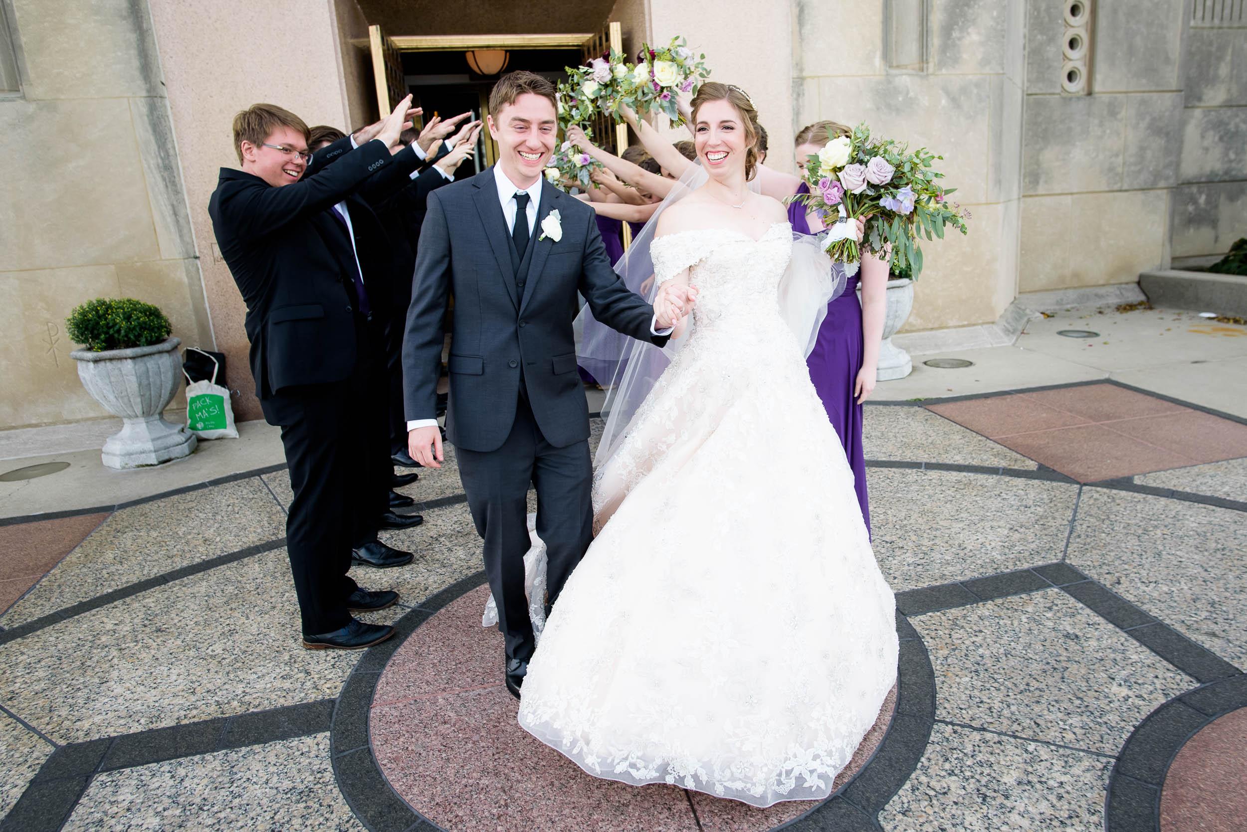 Bride and groom exit the church during a wedding ceremony at Madonna Della Strada.
