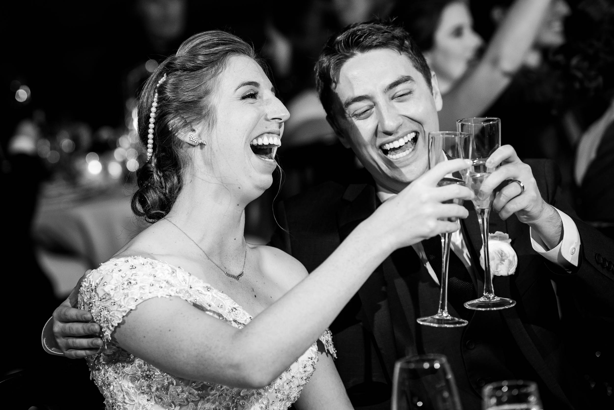 Bride and groom laugh during toasts during a Newberry Library Chicago wedding.