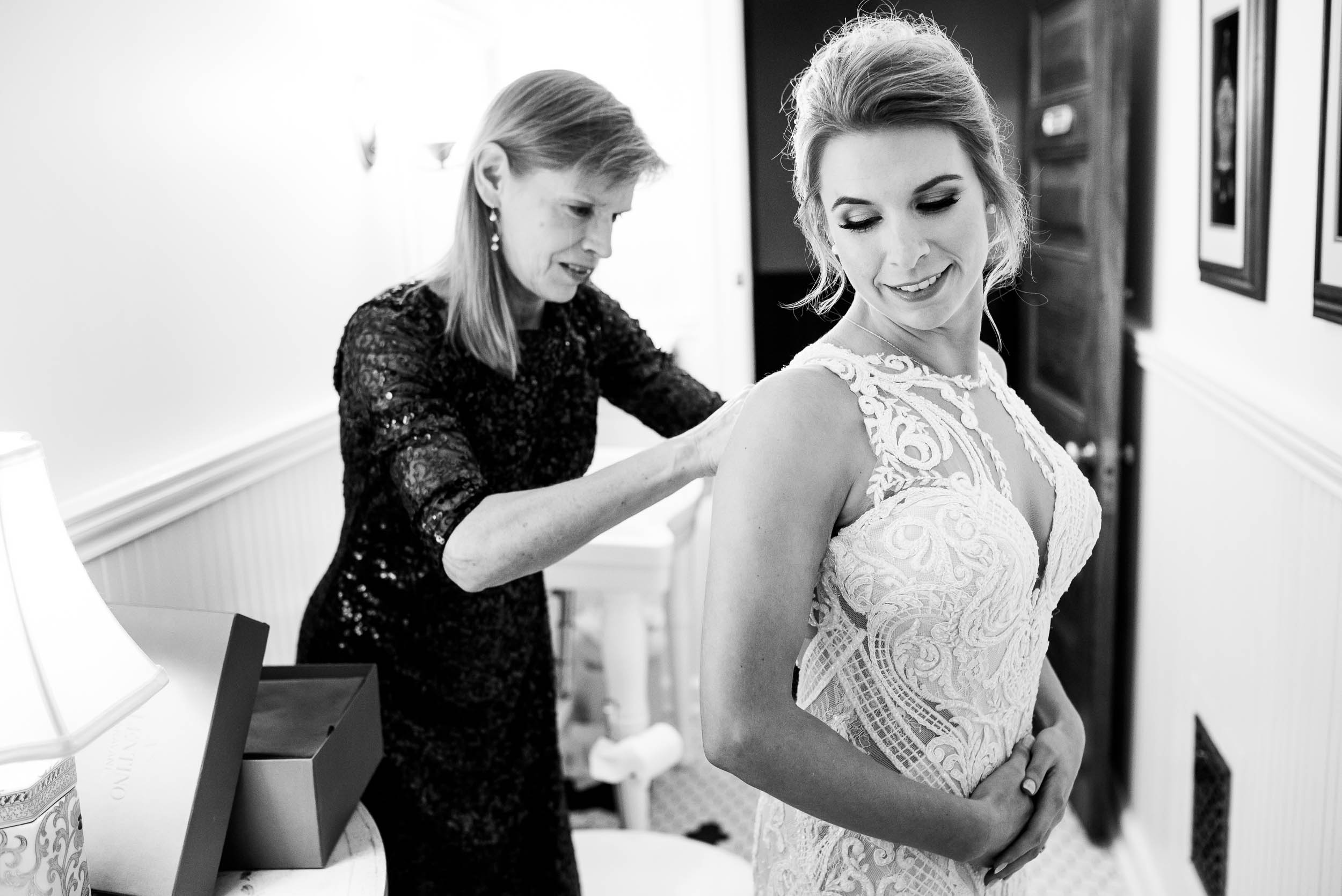 Bride and mom putting on the wedding dress during a Glessner House Chicago wedding.
