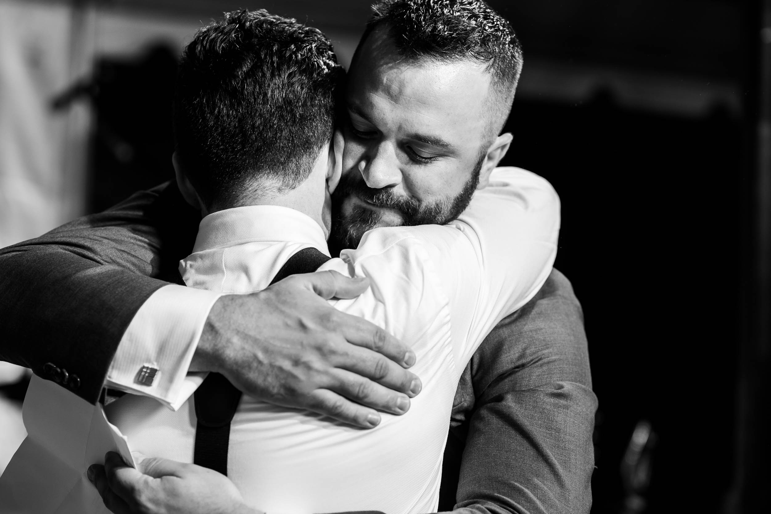 Groom and best man hug during a Glessner House Chicago wedding reception.