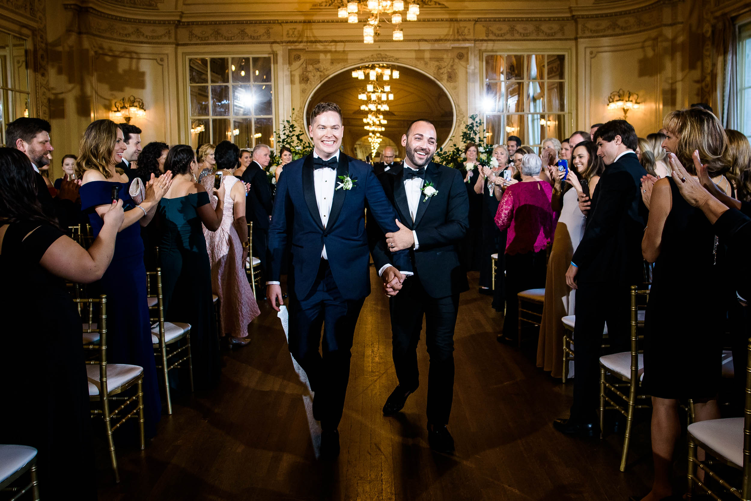 Grooms exiting wedding ceremony for luxurious fall wedding at the Chicago Symphony Center captured by J. Brown Photography. See more wedding ideas at jbrownphotography.com!
