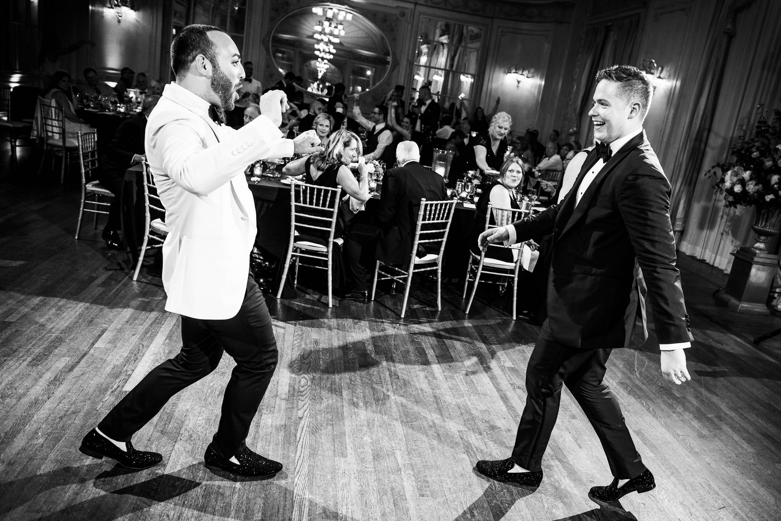Grooms celebrating at luxurious fall wedding at the Chicago Symphony Center captured by J. Brown Photography. See more wedding ideas at jbrownphotography.com!