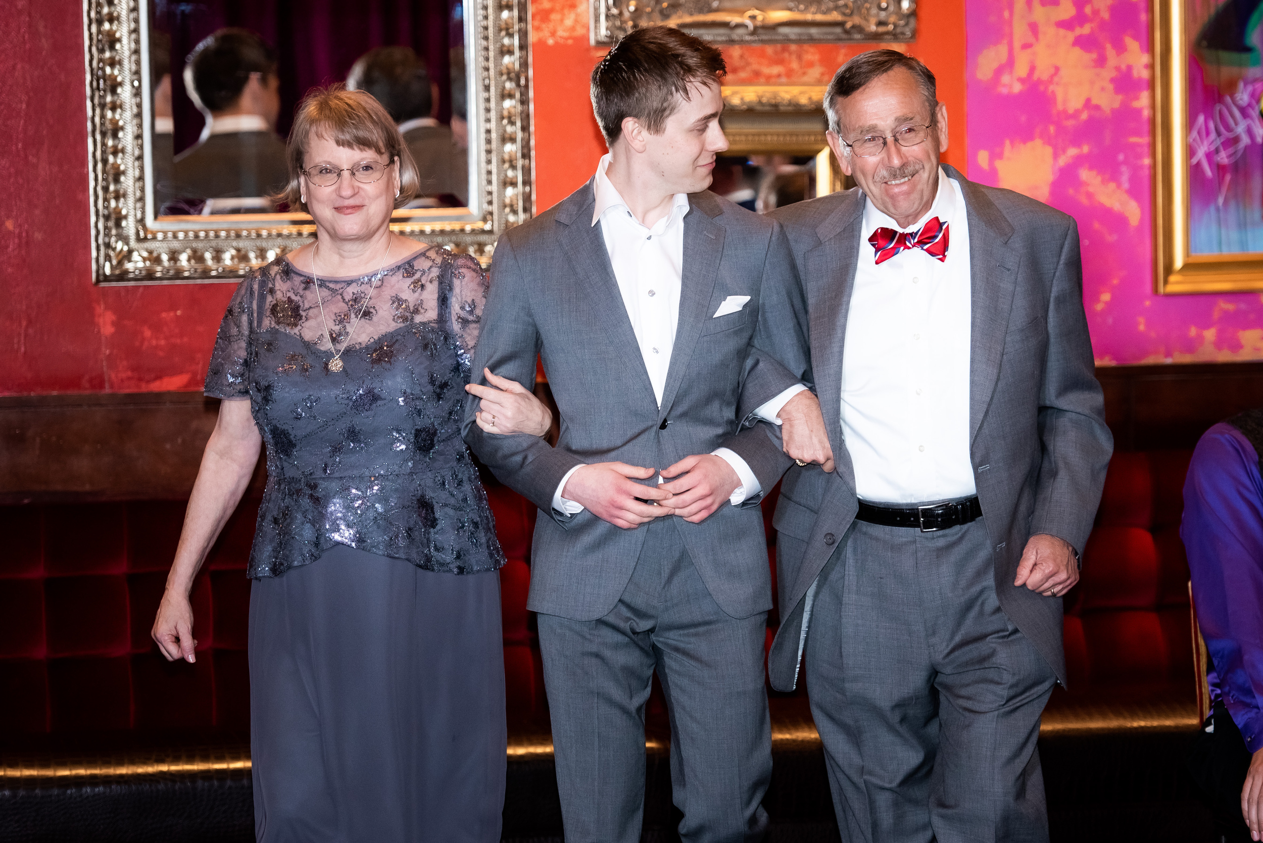 Groom walking into wedding ceremony with parents: Carnivale Chicago wedding captured by J Brown Photography