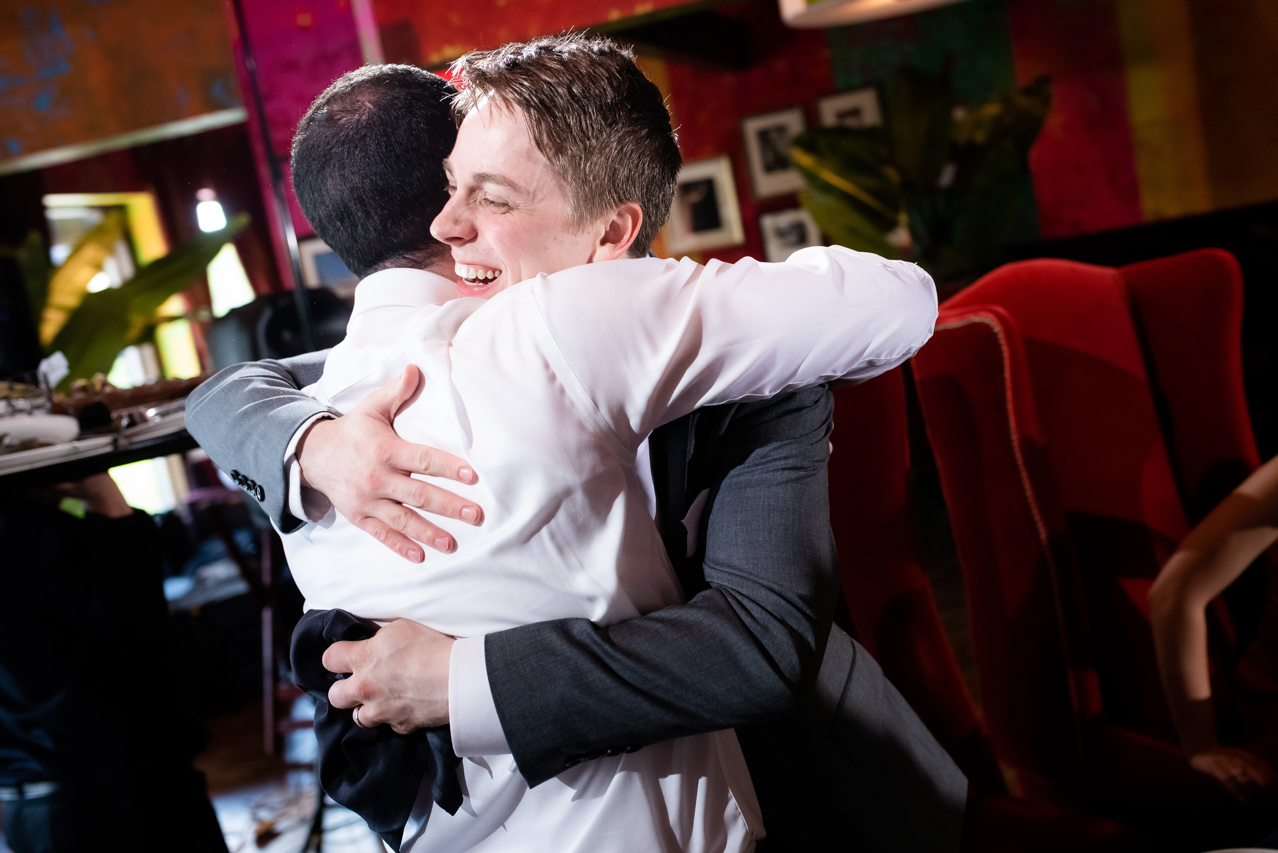 Best man and groom sharing a hug for Carnivale Chicago wedding captured by J Brown Photography