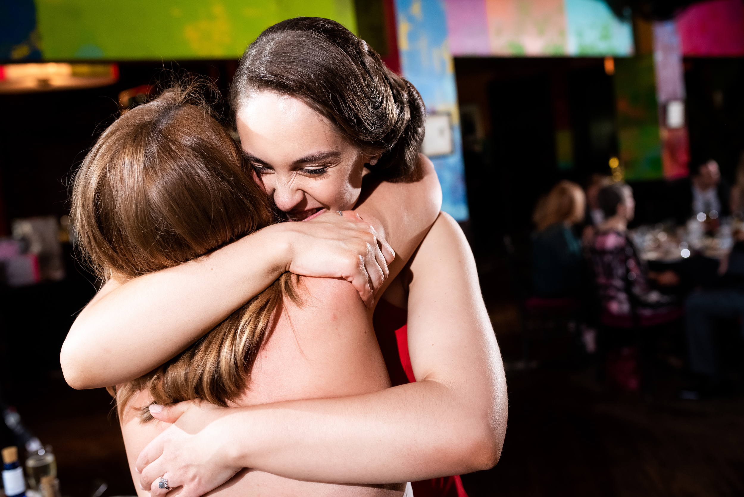 Maid of honor and bride share a hug for Carnivale Chicago wedding captured by J Brown Photography