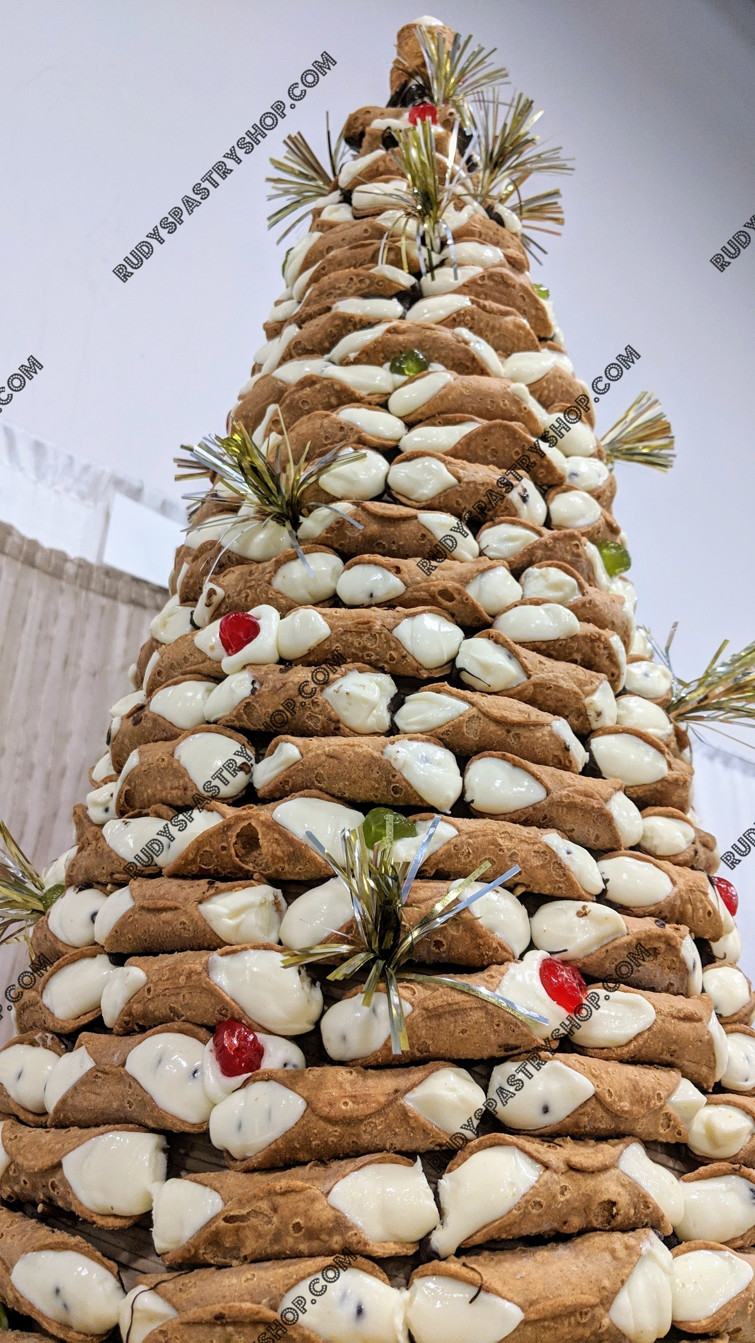 Holy Cannoli Tree - At Rudy's Pastry Shop we want to offer something special and over the top for our customers. Feast your eyes on our 4 Foot Holy Cannoli Tree cake. This delicious beauty will make a delicious center piece to any event you are hosting. Our Cannoli Tree cake is 95% edible.This cake is a fantastic, eye-popping, and fun focal point for your Wedding, Birthday party, Shower, Fundraiser, Company Event, or any Celebration.If this is a bit larger than you may need, we do offer alternate sizes in a 3, 2, or 1 Foot Cannoli Tree cake.Call to order your Cannoli Tree today! 973.743.3768