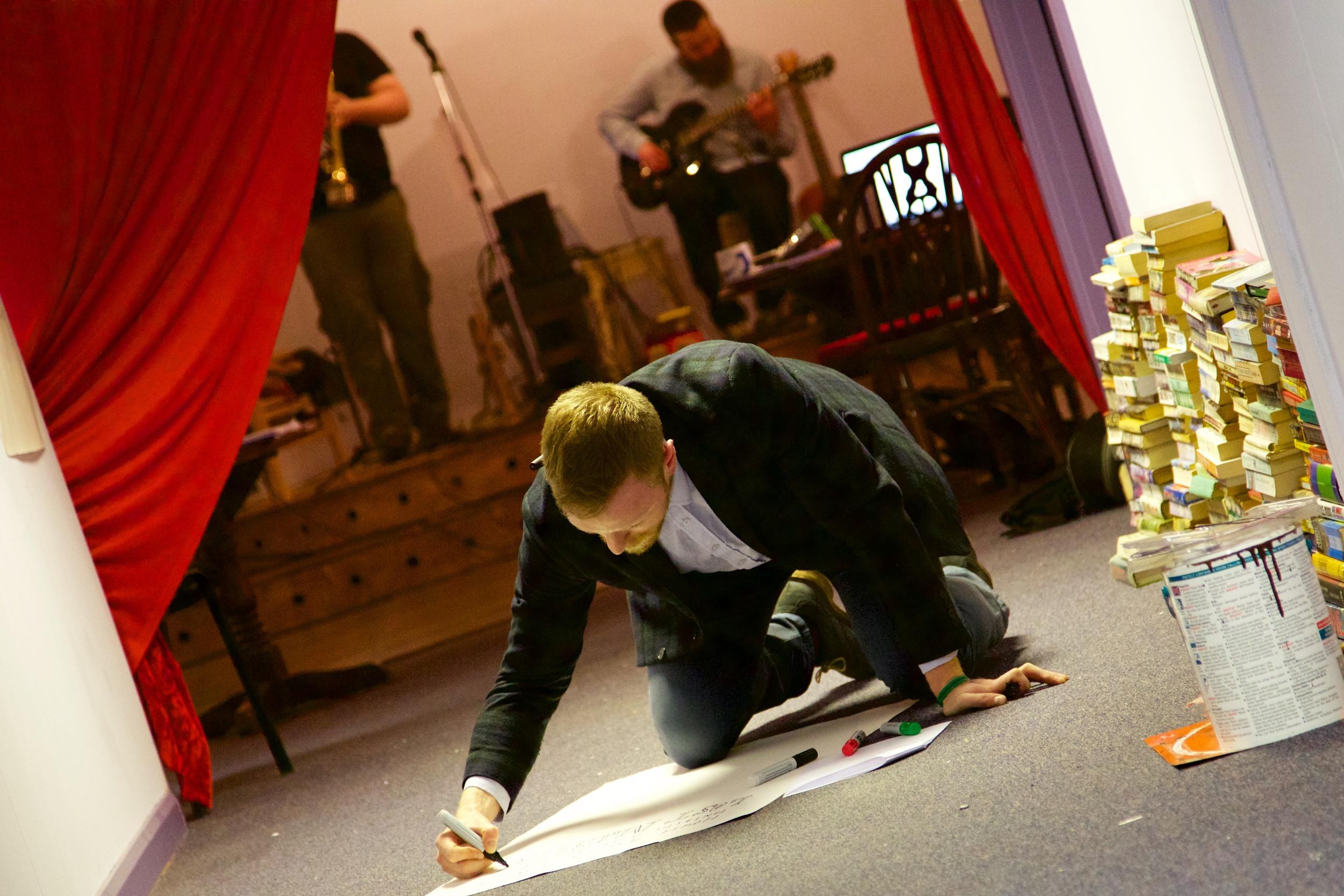 Artist Brian John Spencer workingon signage amidst rehearsals