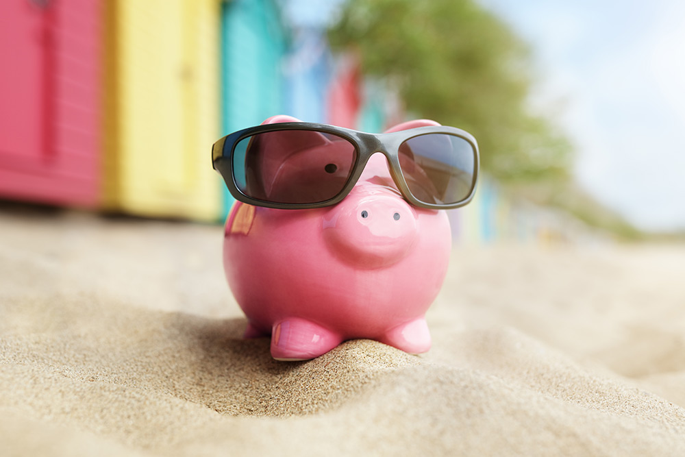 Cute pink piggy bank wearing sunglasses on the beach
