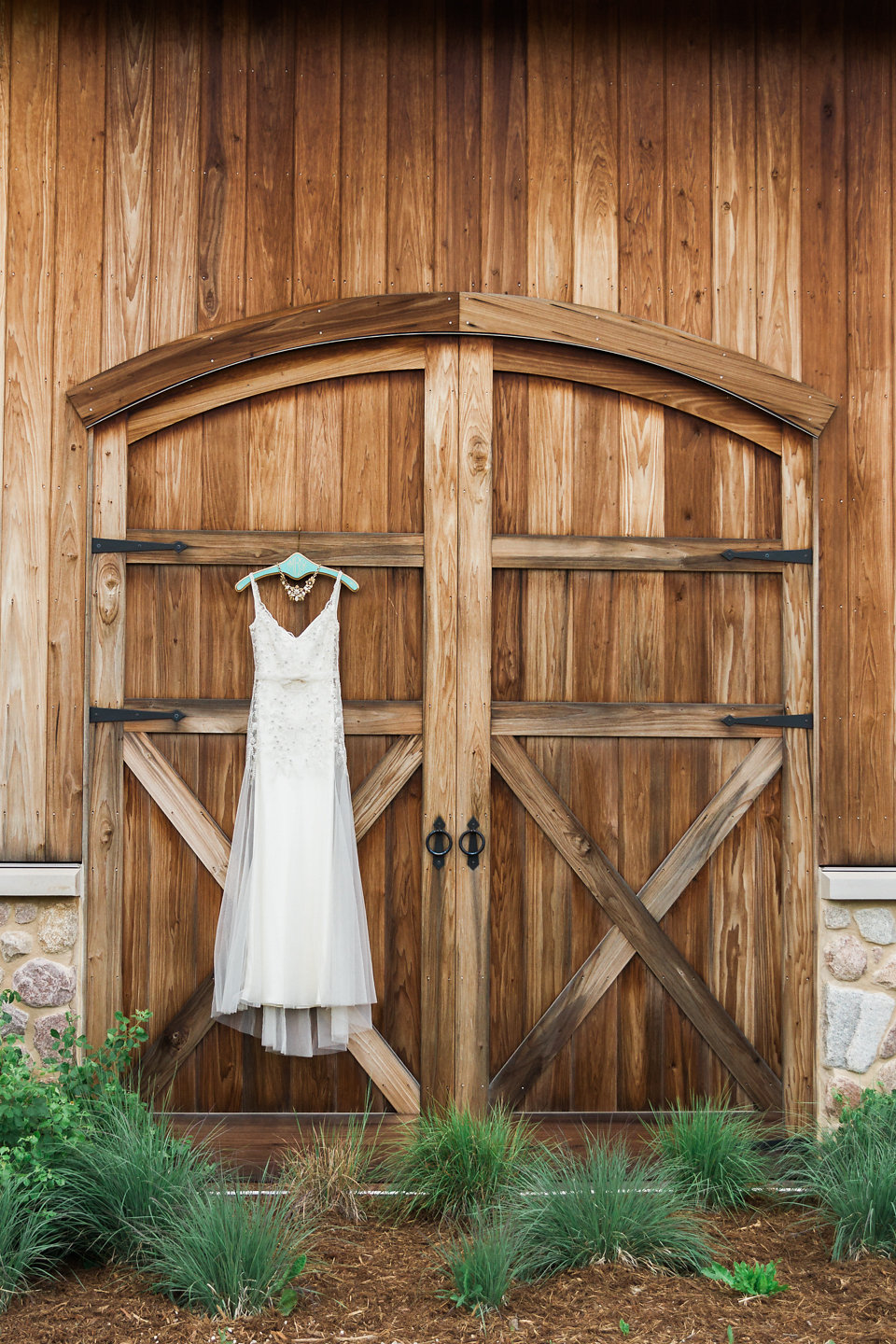 White Wedding Dress Hanging on Barn Doors