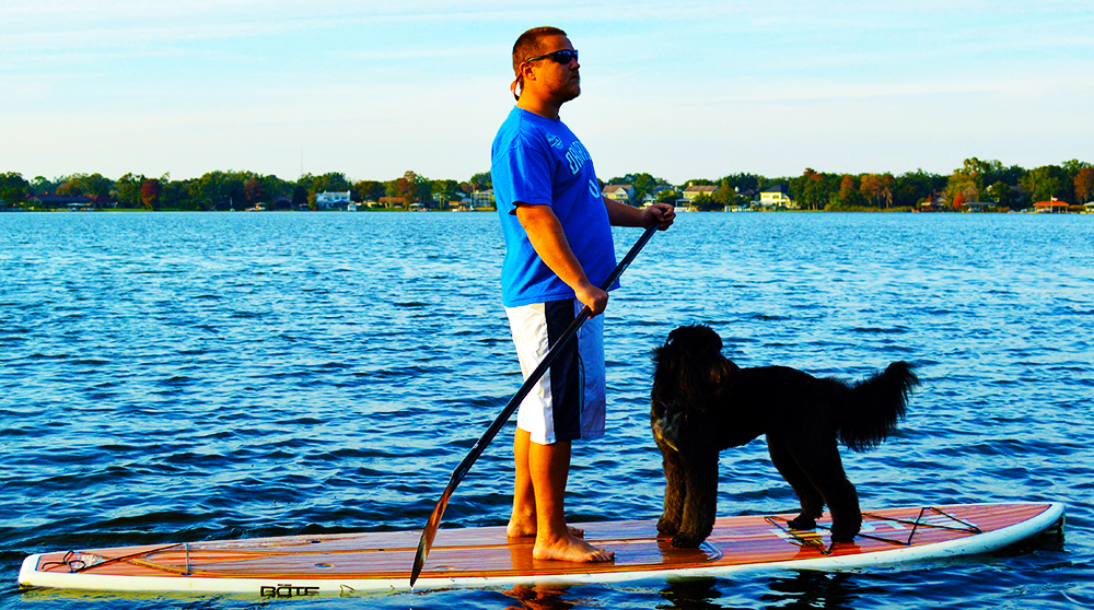 Author Trey Dyer Paddleboarding with his dog, Sammy, in Orlando