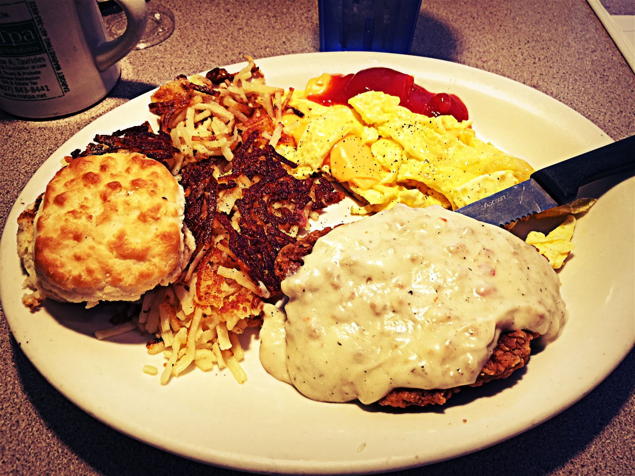 Christos Country fried chicken and gravy with eggs, hashbrowns and a grilled biscuit