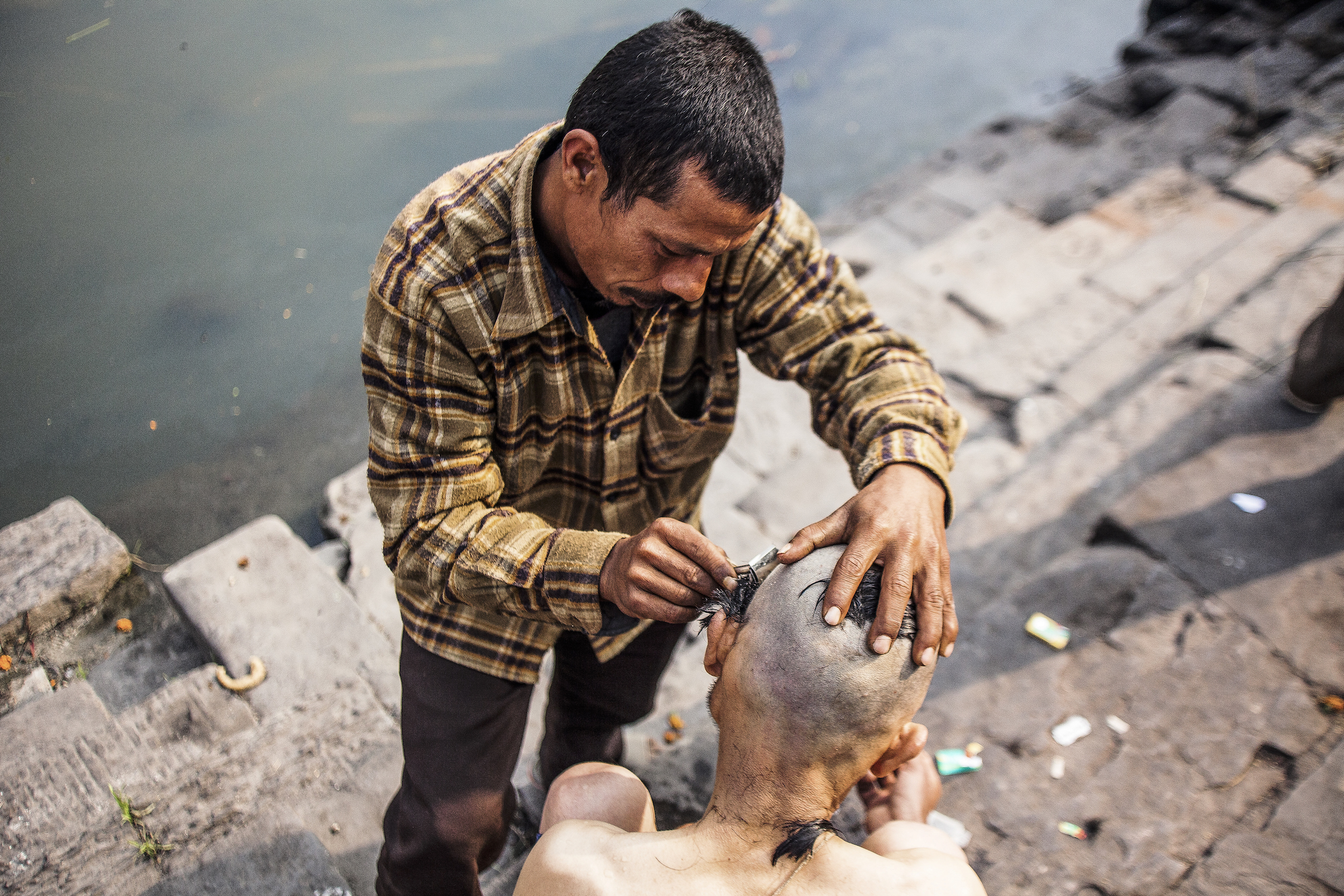 A barber shaves off a man's hair after the cremation of his father in a ritual known as Tonsure—a symbolic offering to the gods, that pays respect to the departed soul.