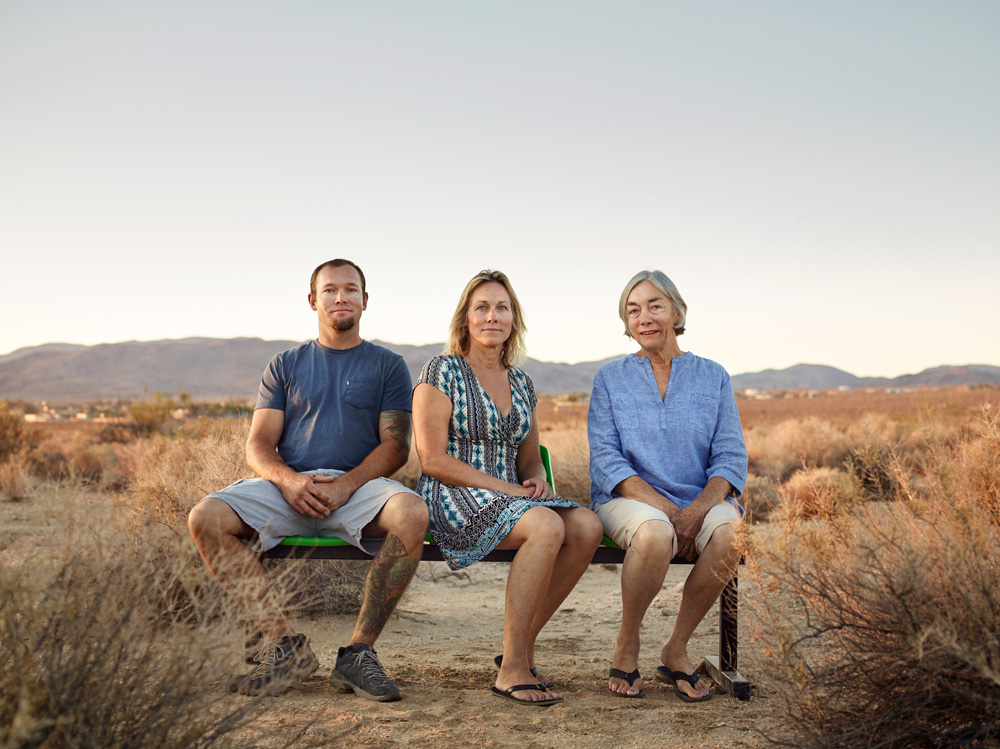 """Heidi and Jane Grunt, 33, 53, 74, Joshua Tree, from the series 'Ages of US' by Dylan Collard. """"This is 3 generations of the Grunt family who run and own the 29 Palms Inn at Joshua Tree National Park. When I was a student I won the Ilford Student Awards, the prize being a trip around California with a photographer. One of the places we stayed at on that trip was the 29 Palms Inn and its a place I loved and always wanted to return to. So I made their hotel one of the focal points of my trip and arranged with them that I'd photograph each generation of their family as part of the project."""""""