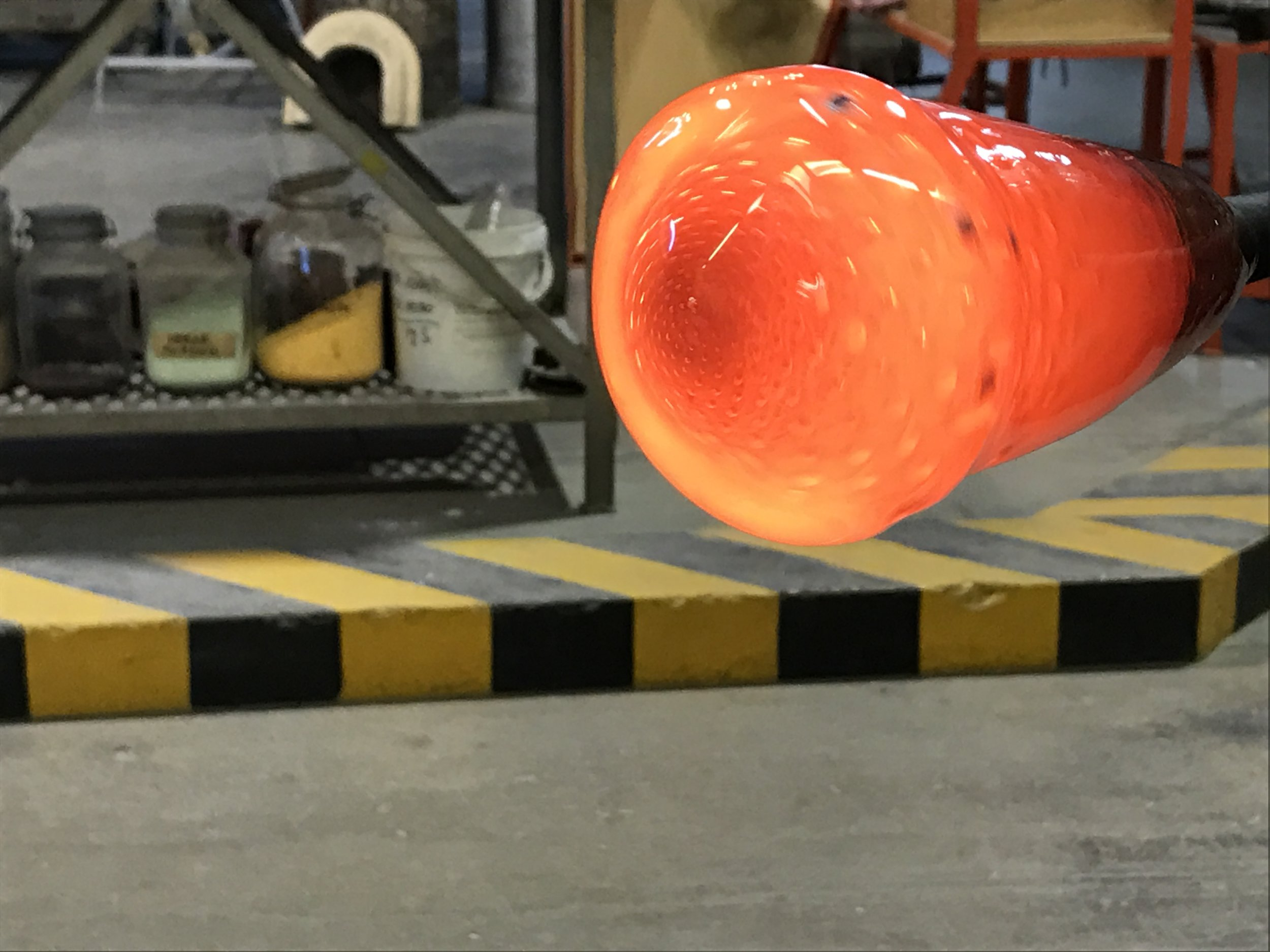 Very hot glass being made into a vase