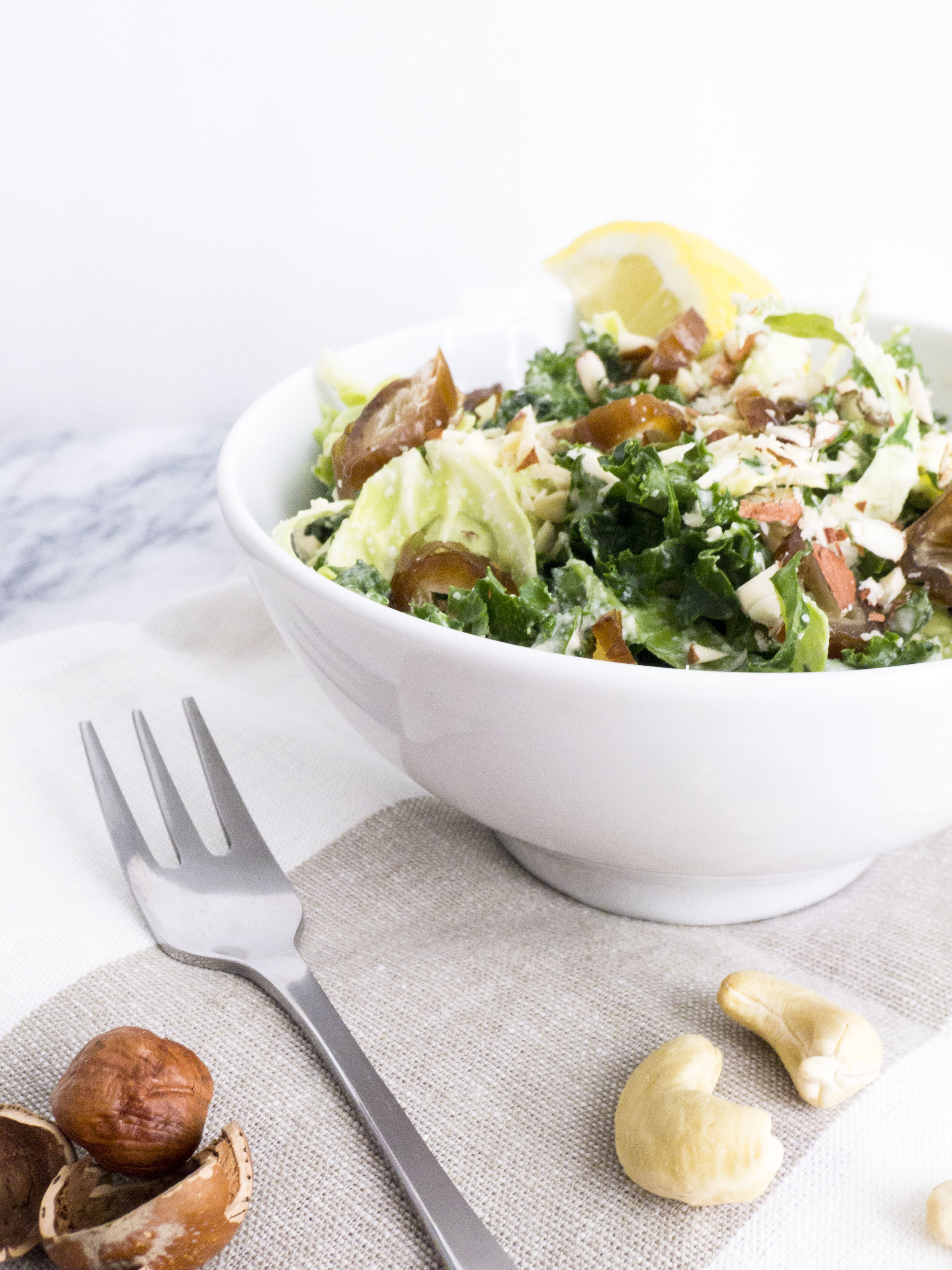 kale and shaved brussels sprout salad with cashew mayo, hazelnuts and dates