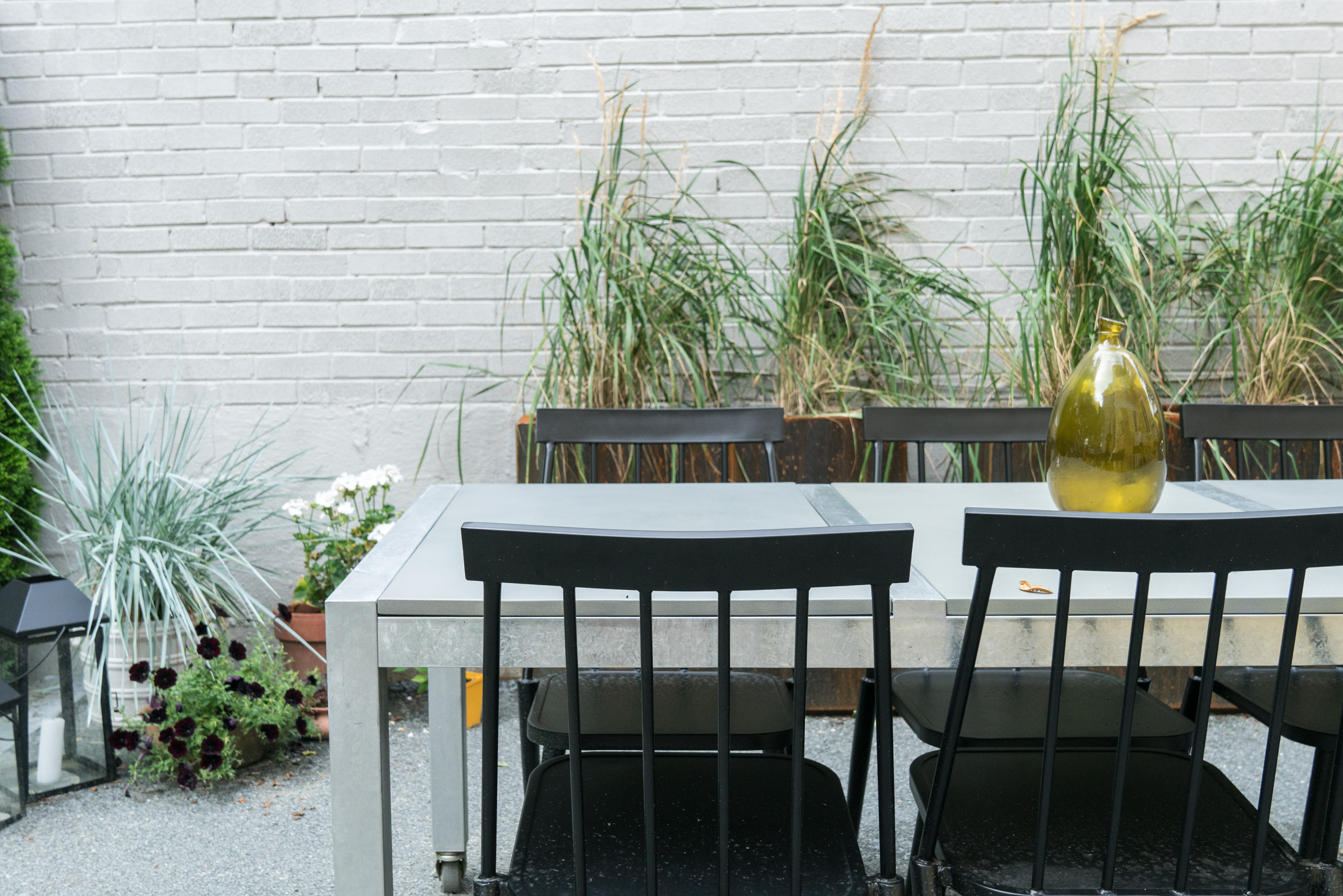 corten steel planters with grass, concrete outdoor dining table