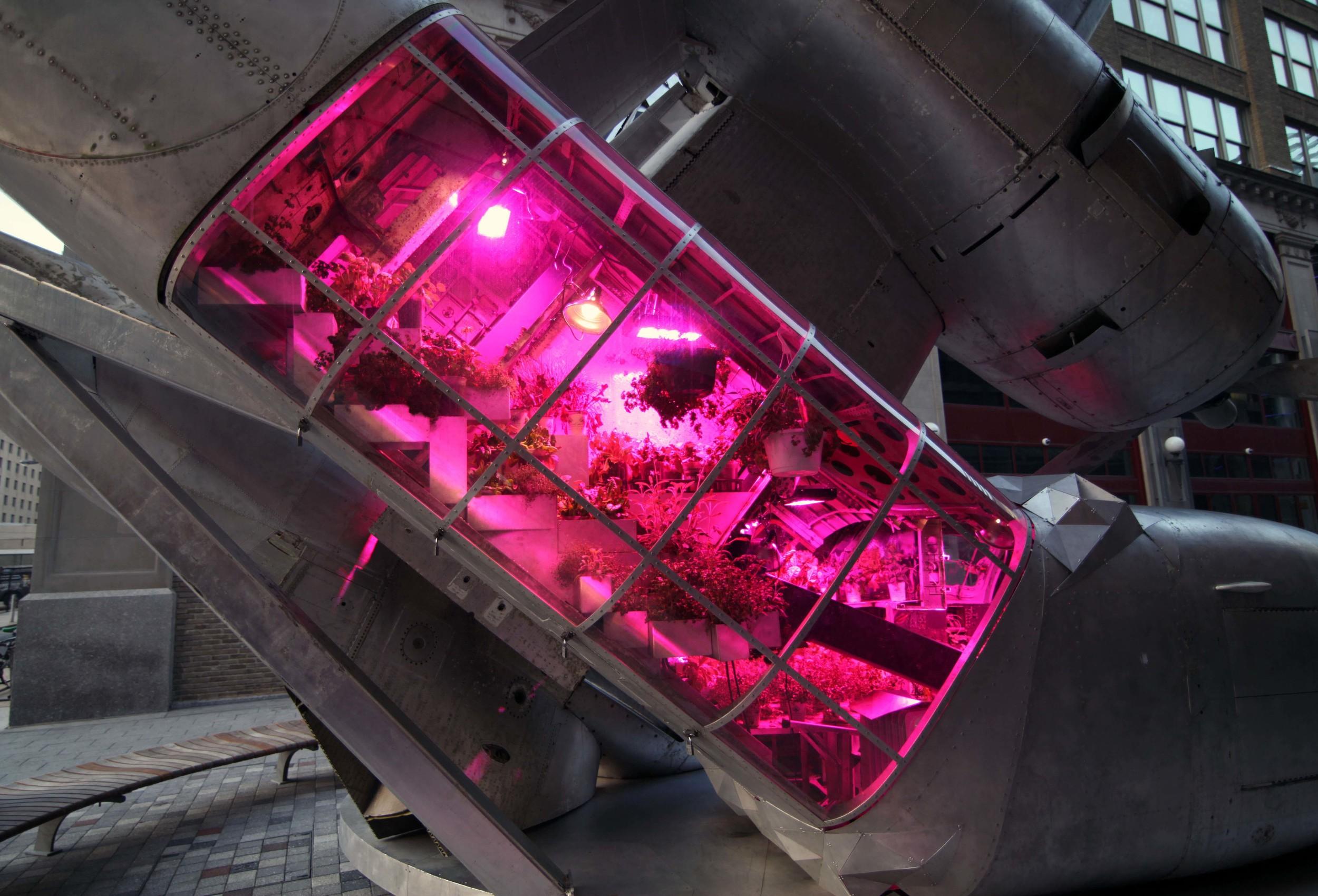 Grumman Greenhouse, 2011, Grumman S2f Cold War Era submarine tracking torpedo bomber, solar panels, edible vegetables and herbs, 30' tall 18' wide 20' deep.