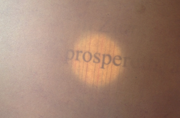Shining a flashlight from behind the paper illuminates the words.