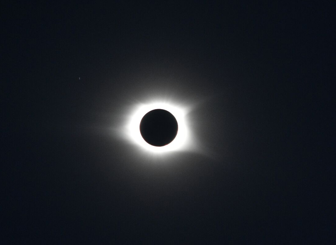 This is a photo I took, with my comparatively modest 200mm lens. Still pretty proud of it though: This involved setting up my camera on a tripod pointing almost directly overhead, covering it with a makeshift eclipse filter, and then during totality manually adjusting settings and focus with my fingertips.