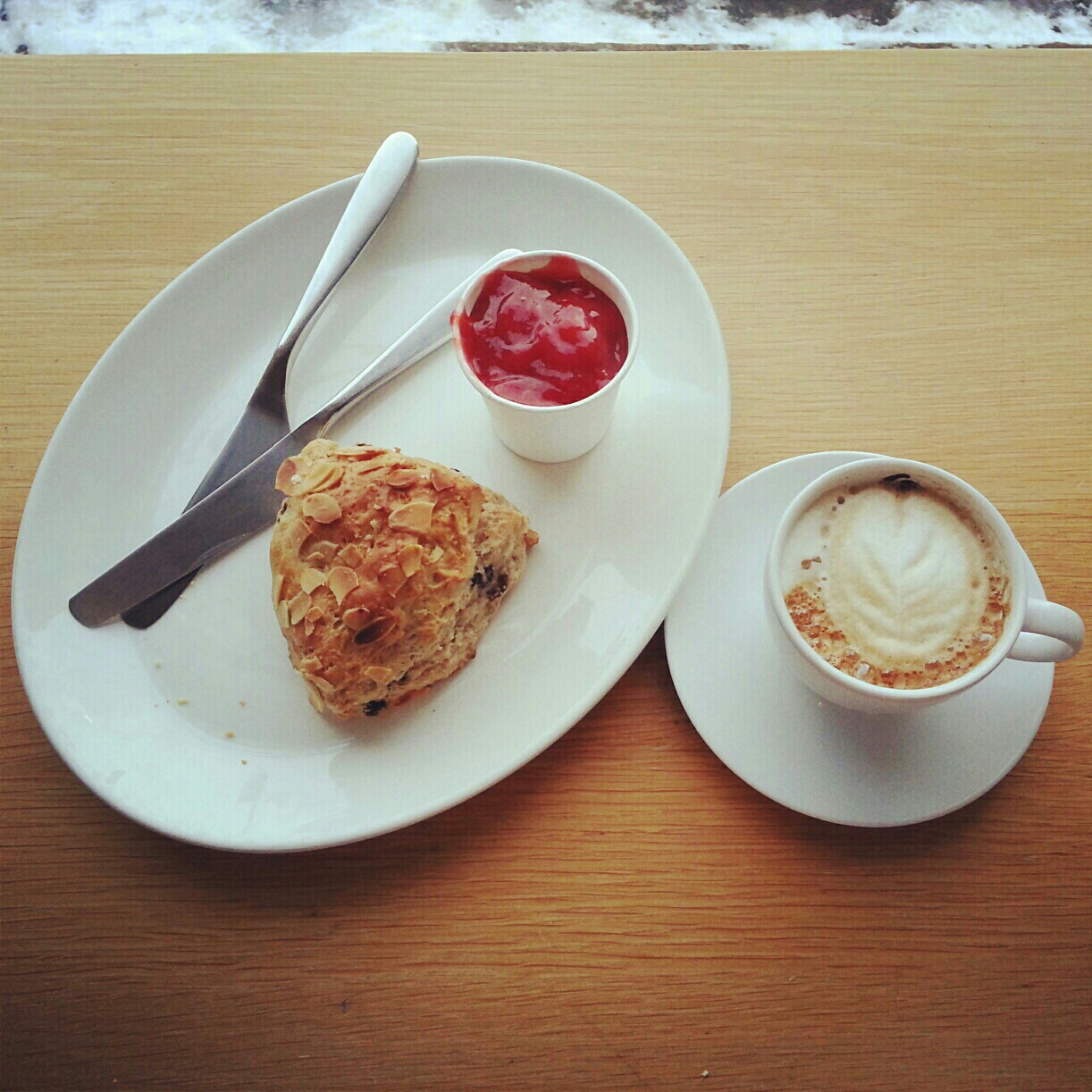 Freshly baked scone with housemade jam and cappuccino