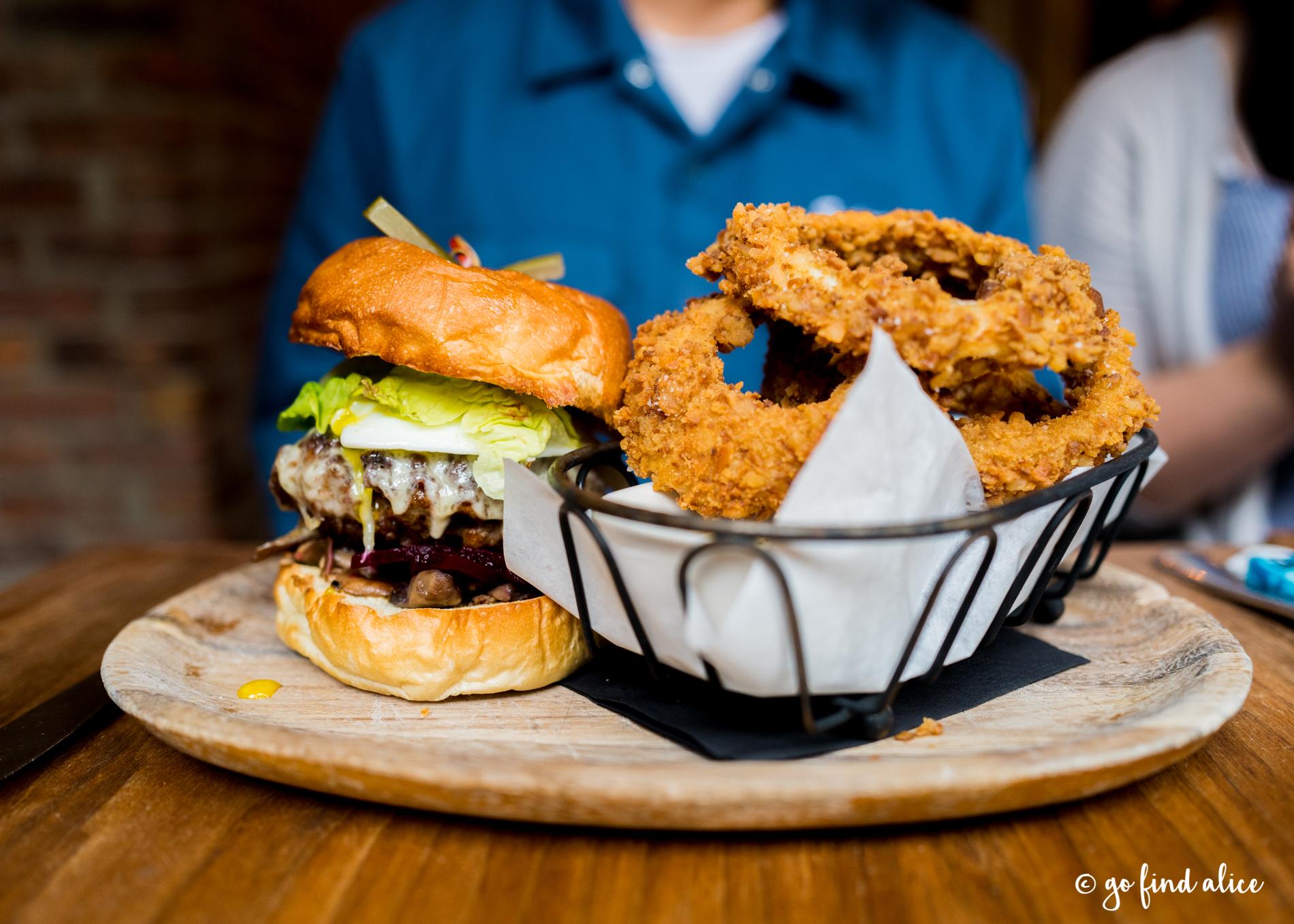 Highlands Burger, Black Angus, Pickled Beet, Scottish Cheddar, Fried Egg, Mushrooms, Black Garlic-Horseradish Aioli, Pretzel Crusted Onion Rings ($17)
