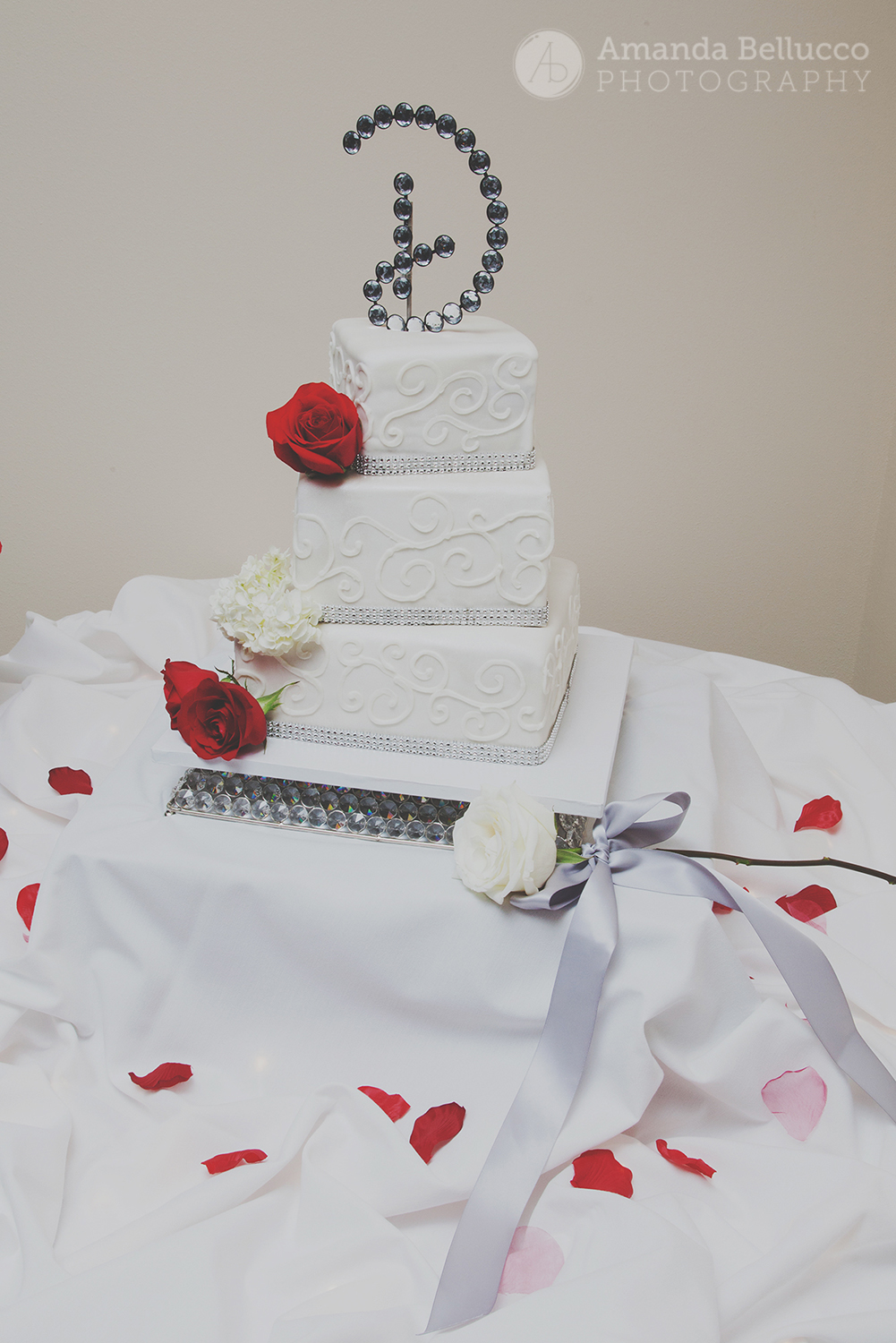 Three tier wedding cake with roses during the reception at the Italian American Community Center.