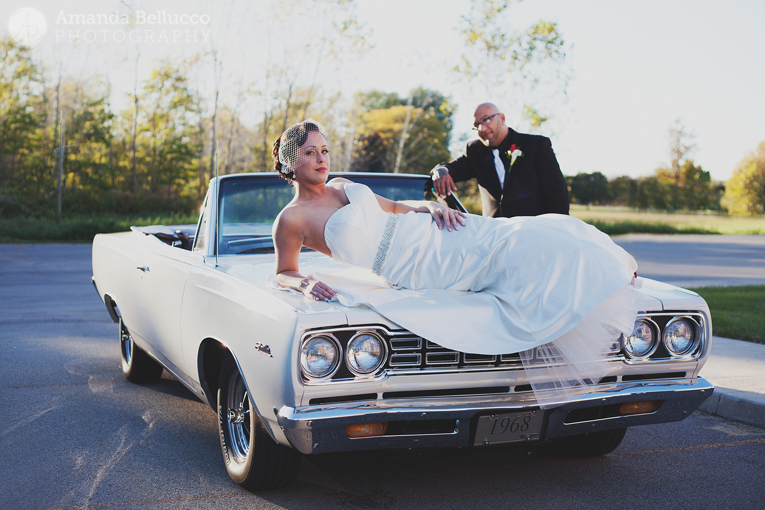 The bride and groom pose for wedding photos with a vintage convertible at the Italian American Community Center.