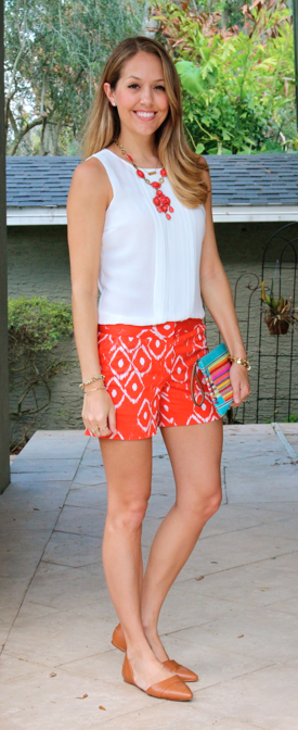 White pleated top, red tribal shorts, rainbow clutch